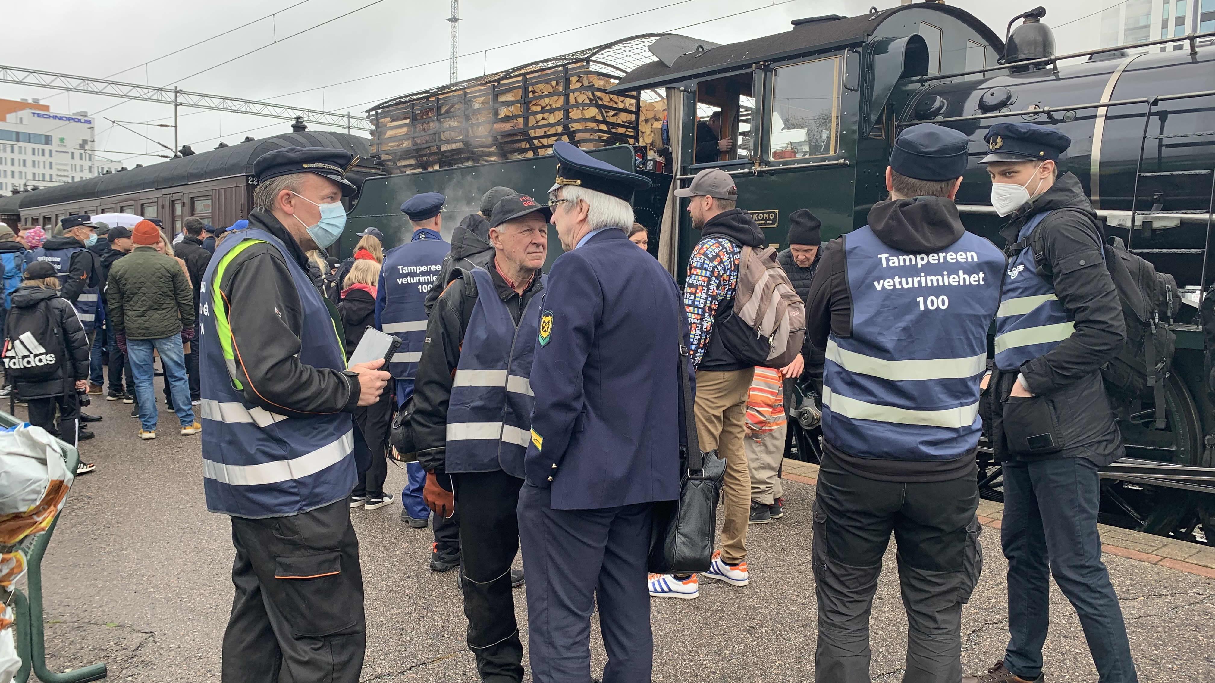 Veturinkuljettajia ja muita ihmisiä menossa höyryveturin vetämän junan kyytiin