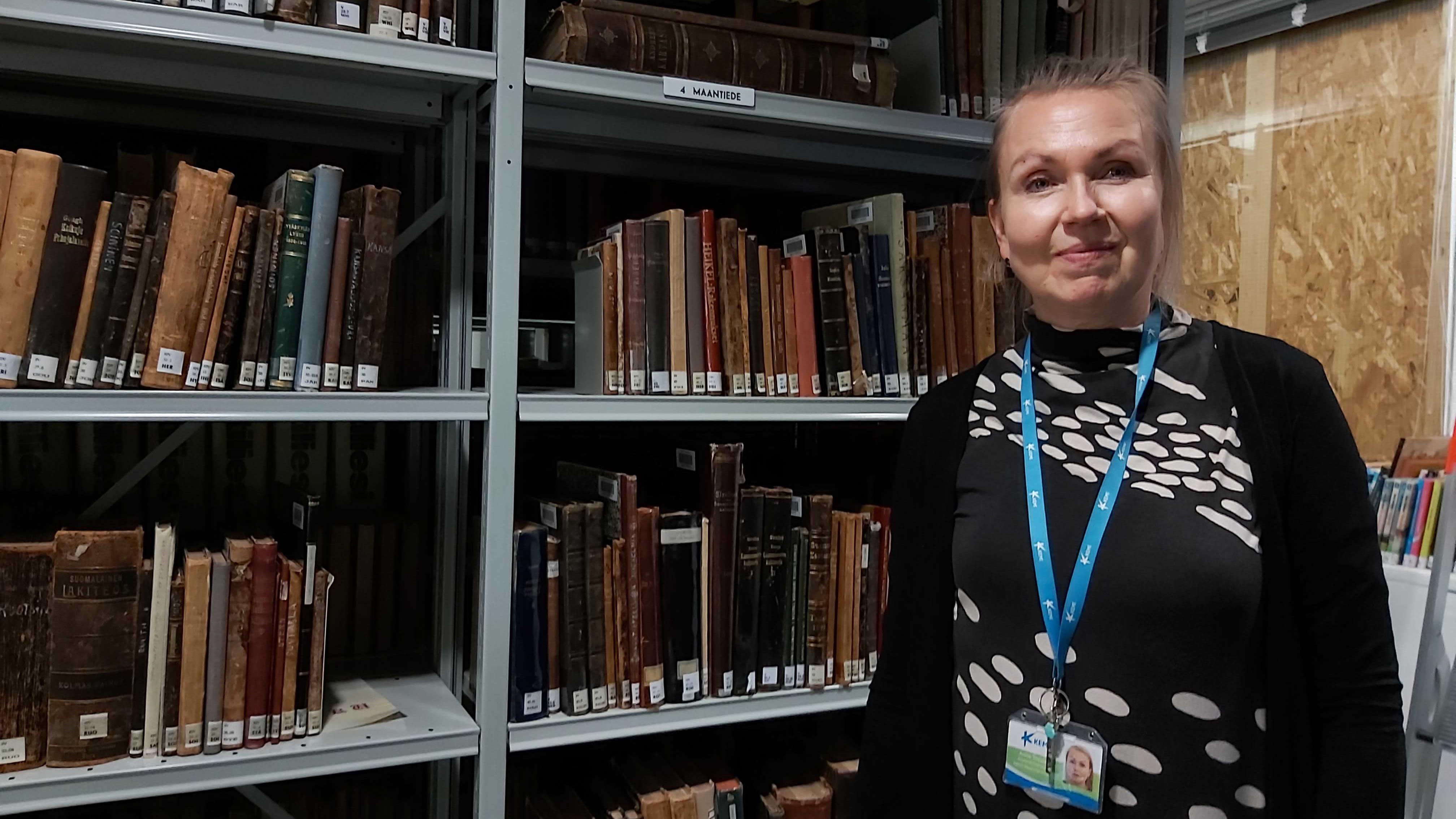 Kemin vapaa-aikapäällikkö Anne Toppari seisoo kirjavarastossa kirjahyllyn edessä.