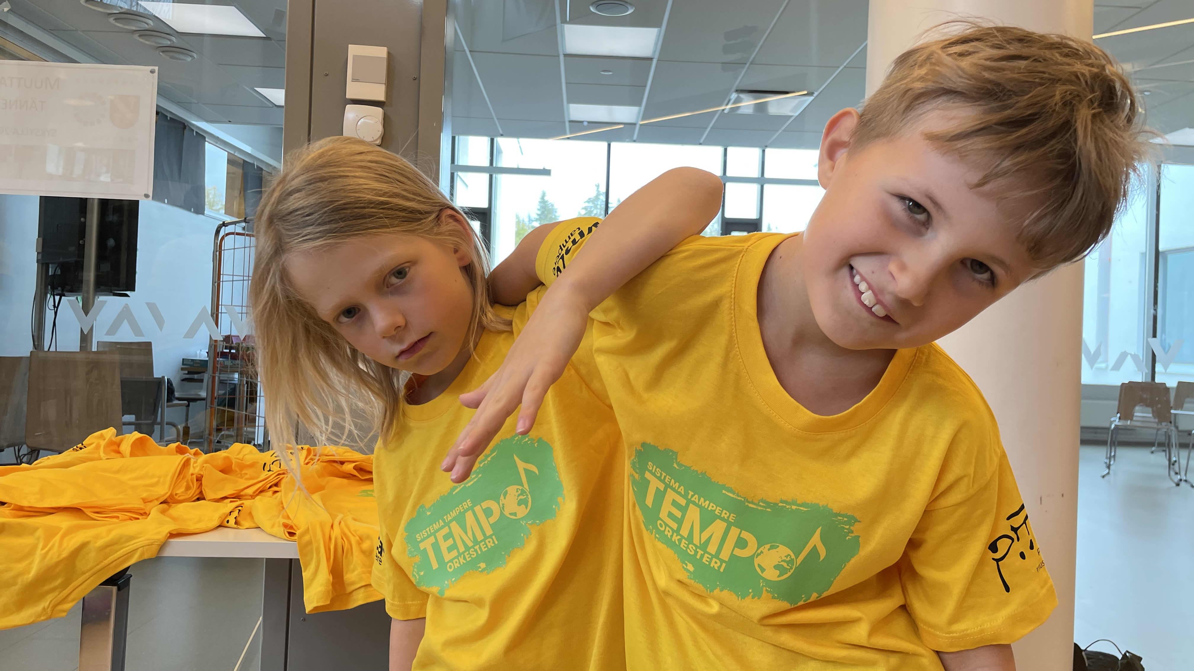 Tokaluokkalaiset Vilho Jokinen ja Jasper Nummenmaa keltaisissa Tempo-orkesterin t-paidoissaan kaulailevat