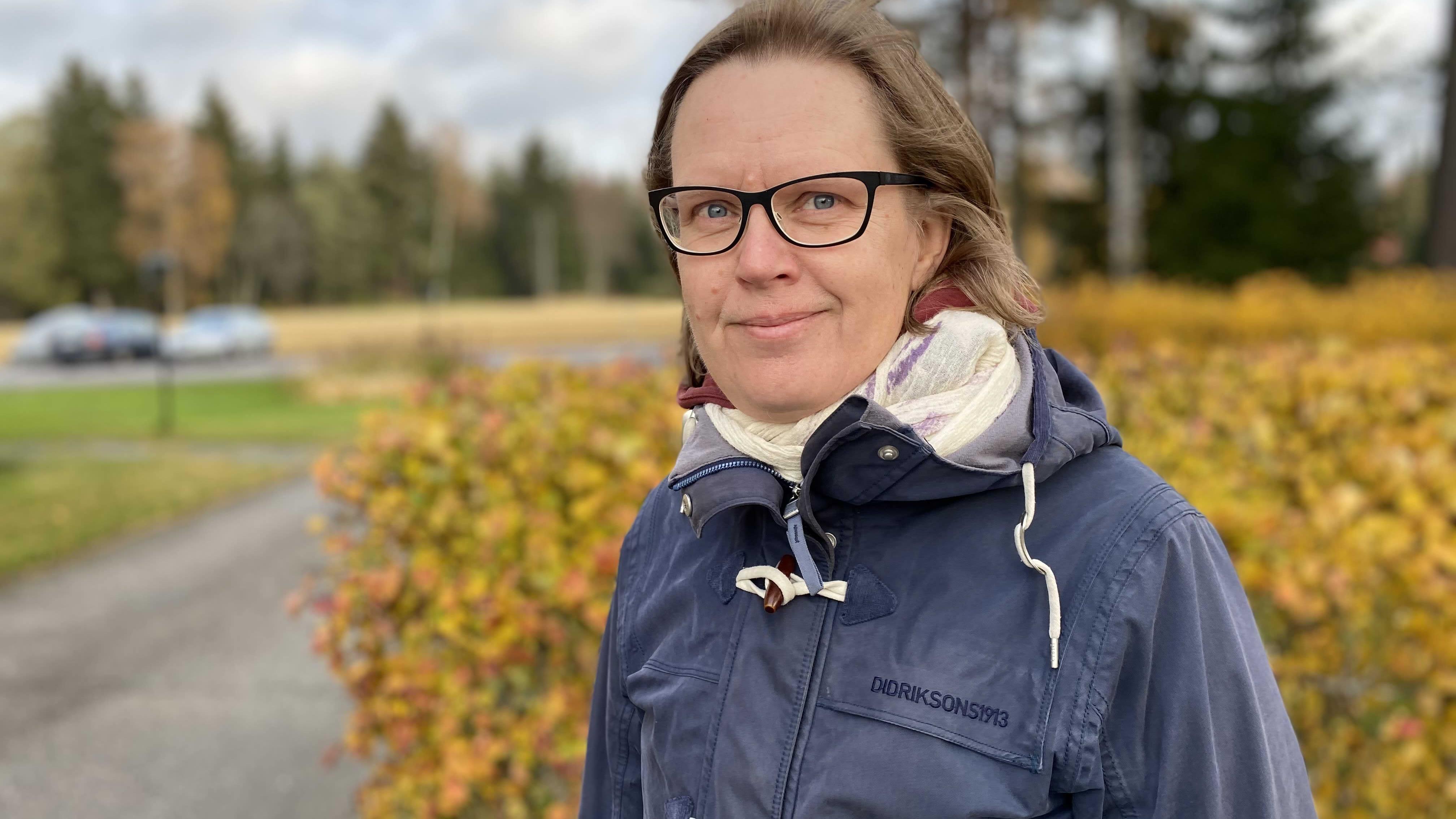 Kyläasiamies Elina Leppänen katsoo hymyillen kameraan sininen takki yllään. Taustalla ruskan värjäämiä pensaita.Tuuloksessa 4.10.2021.