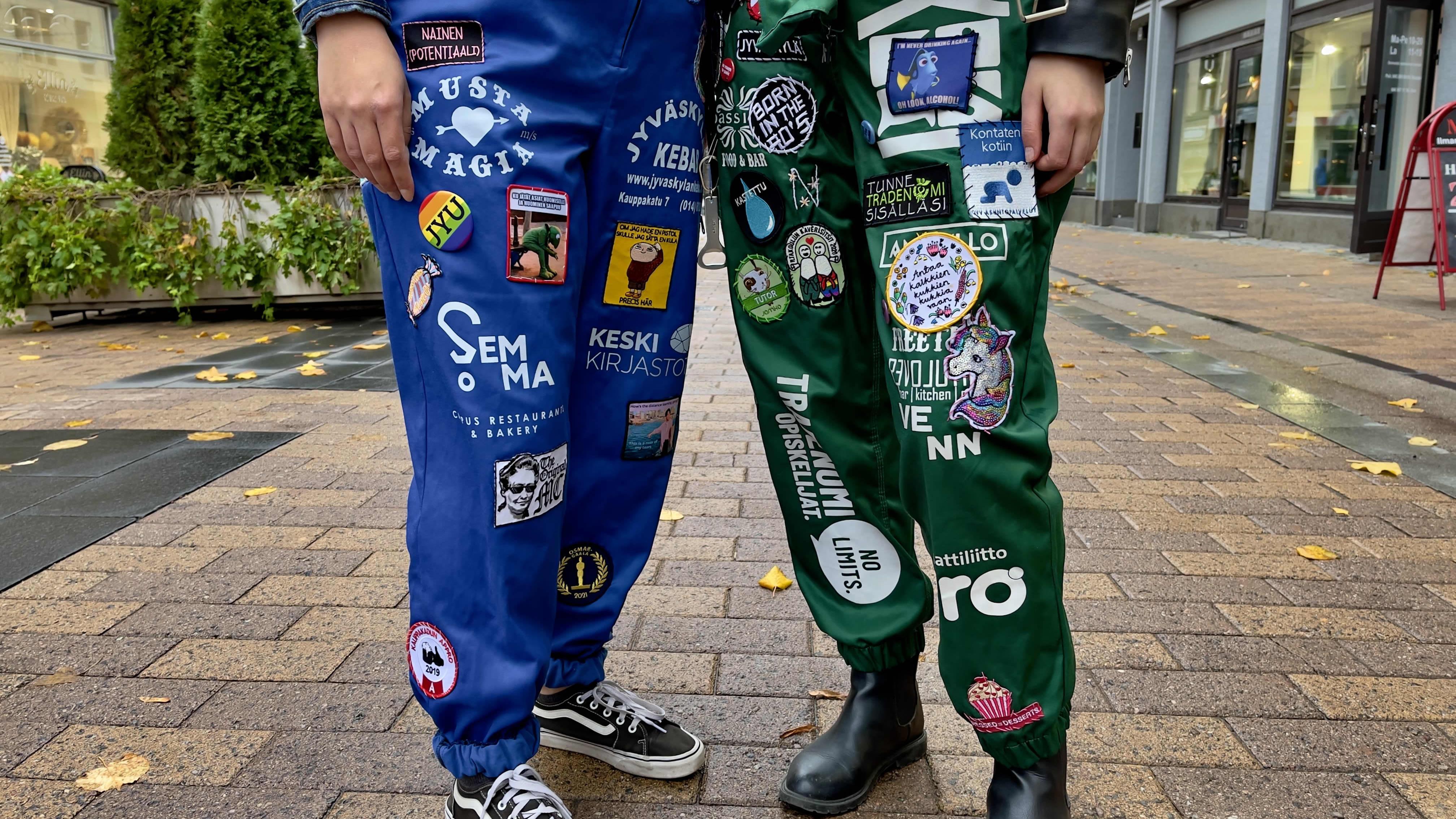 Kaksi opiskelijaa seisoo kadulla, toisella sininen haalari ja toisella vihreä. Molemmissa paljon merkkejä.