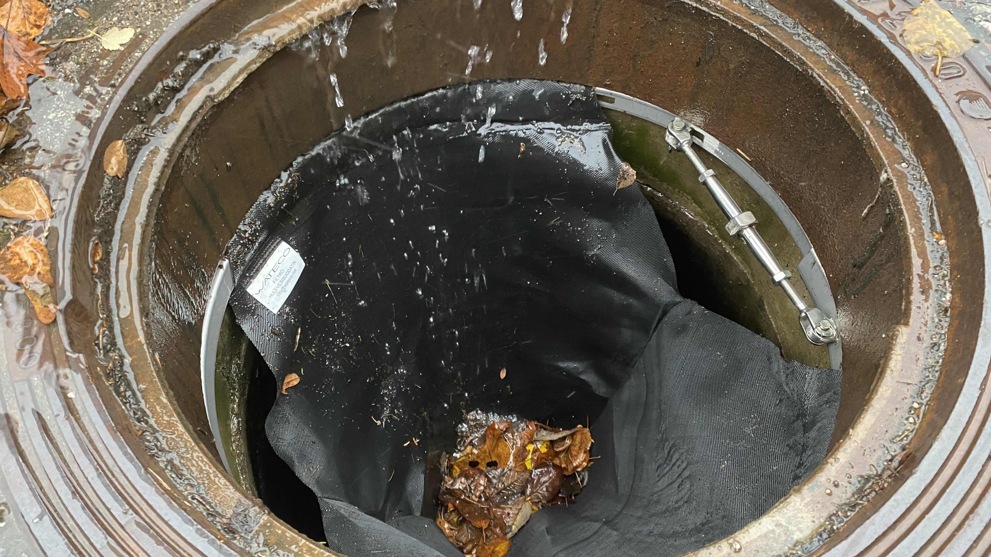 Avattu sadevesikaivo, jossa näkyy musta suodatuskangas sisällä. Suodattimeen on jäänyt lehtiä.