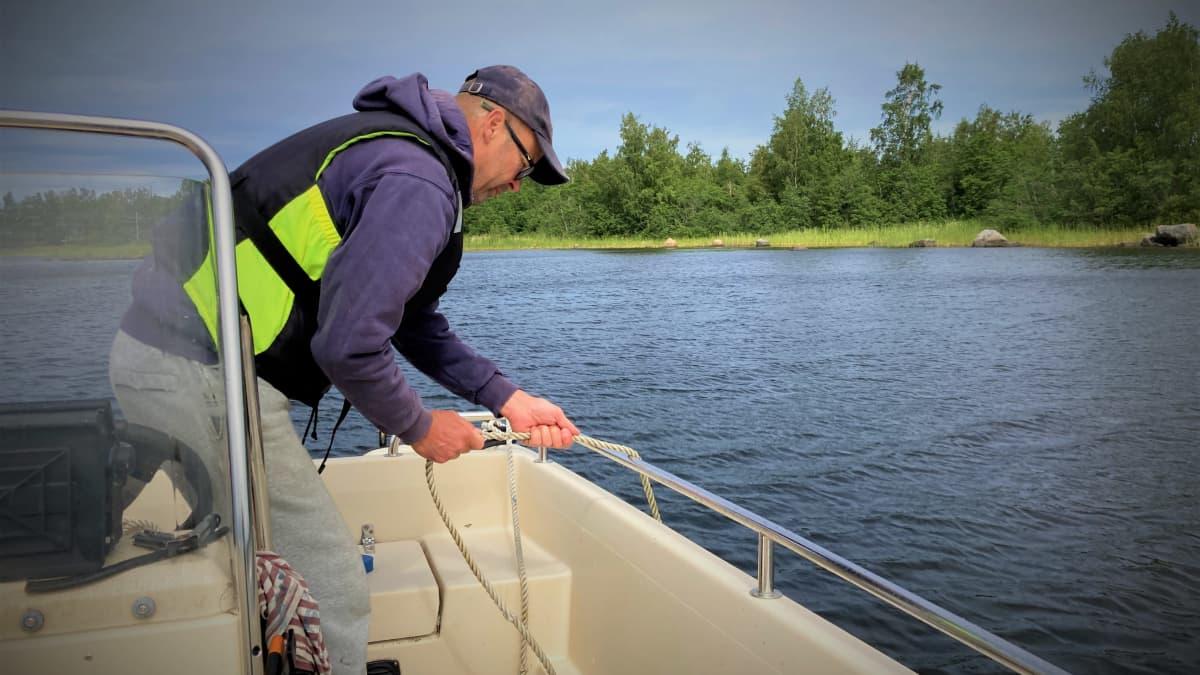 Kalastus- ja luonto-opas Jukka Viita-aho laskee veneen ankkuria veteen.