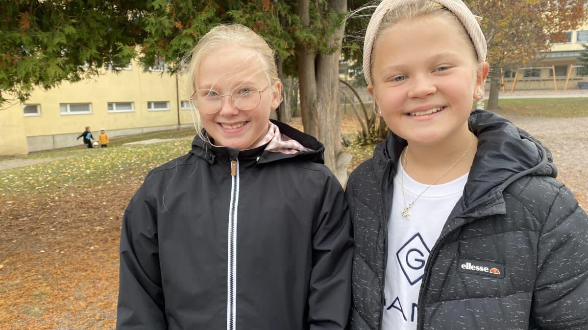 Seminaarin koulun viidesluokkalaiset, vaaleatukkaiset Kukka Oksanen ja Fia Hirvonen katsovat kameraan hymyillen syksyisellä koulun pihalla mustissa takeissaan. Kuva otettu 11.10.2021.
