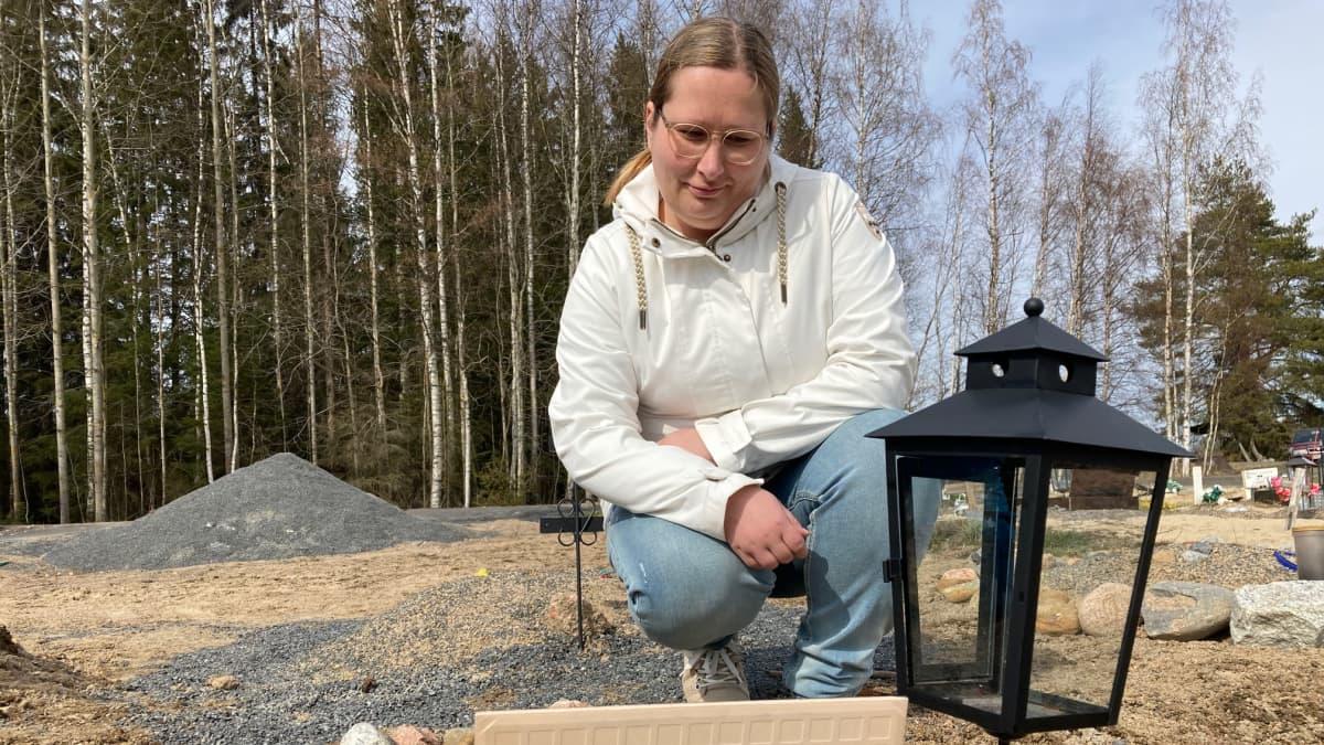 Anna-Maria Soini istuu koiransa Viljon hautapaikan luona Seinäjoen lemmikkieläinten hautausmaalla.