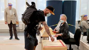 Vaalipaikalla viimeinen äänestäjä luovuttaa äänestyslappunsa.