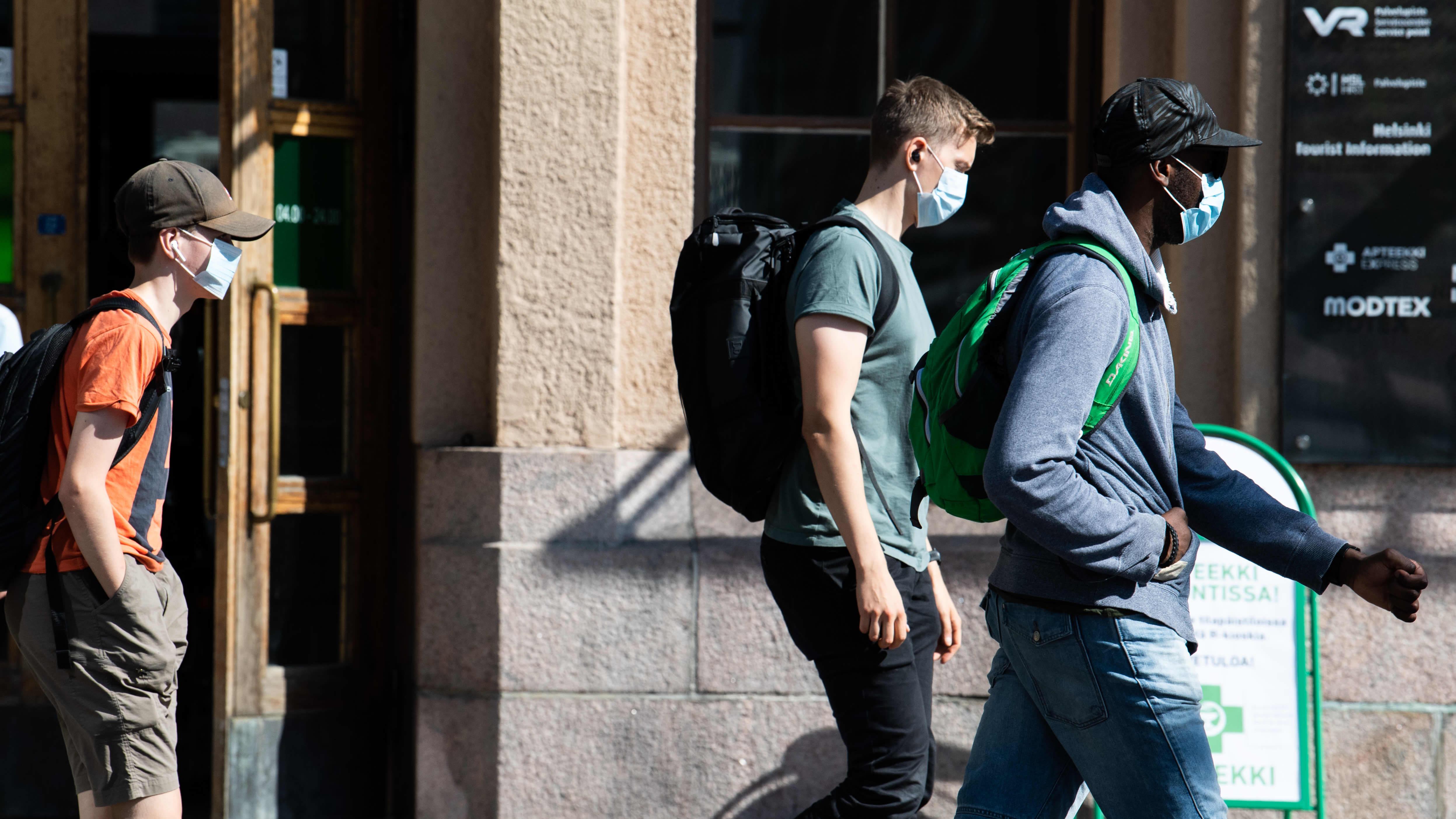 Ihmisiä kiirehtii junalta kasvomaskeihin suojautuneena Helsingin rautatieasemalla.