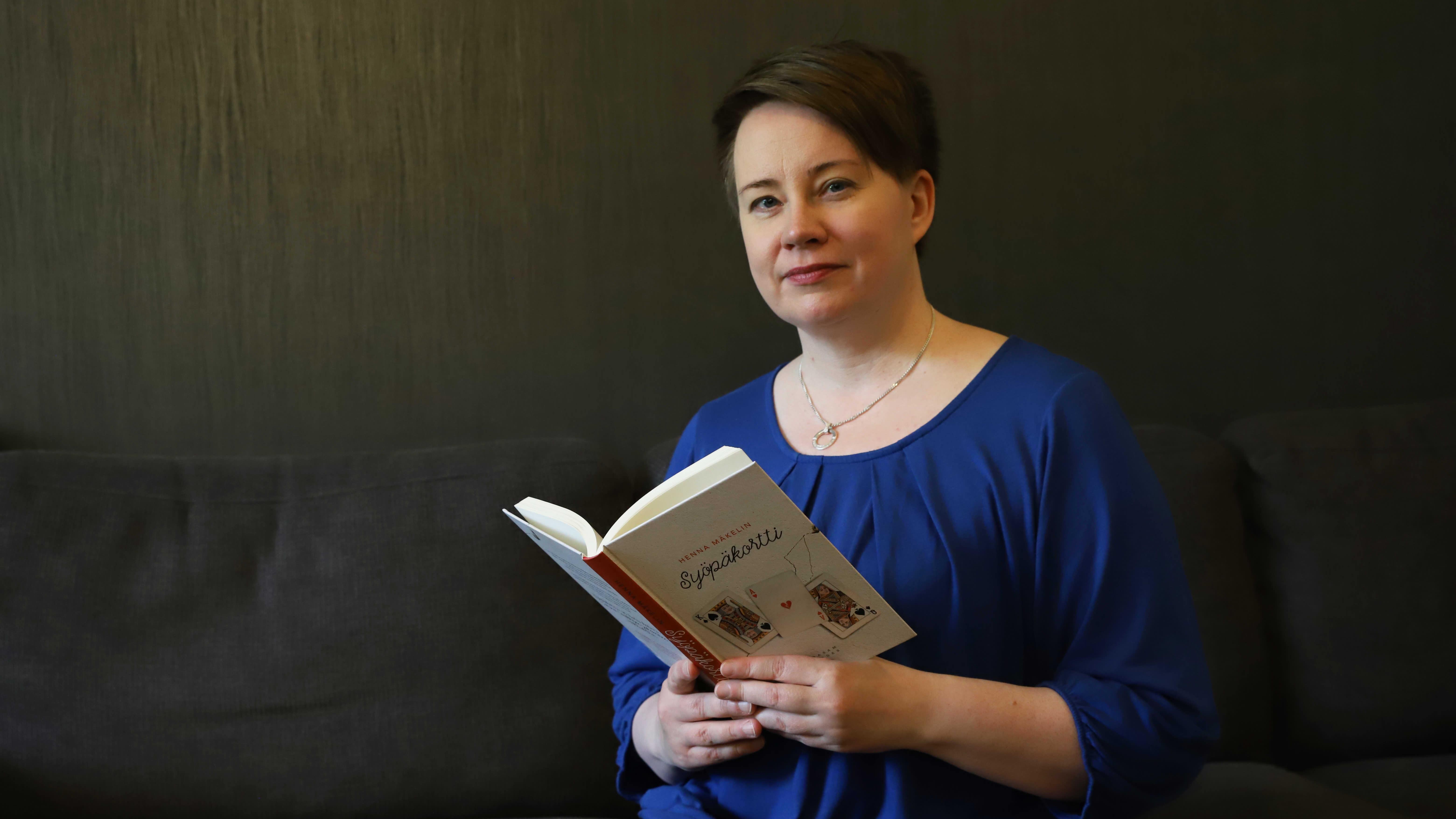 Kirjailija Henna Mäkelin pitelemässä Syöpäkortti -kirjaansa.