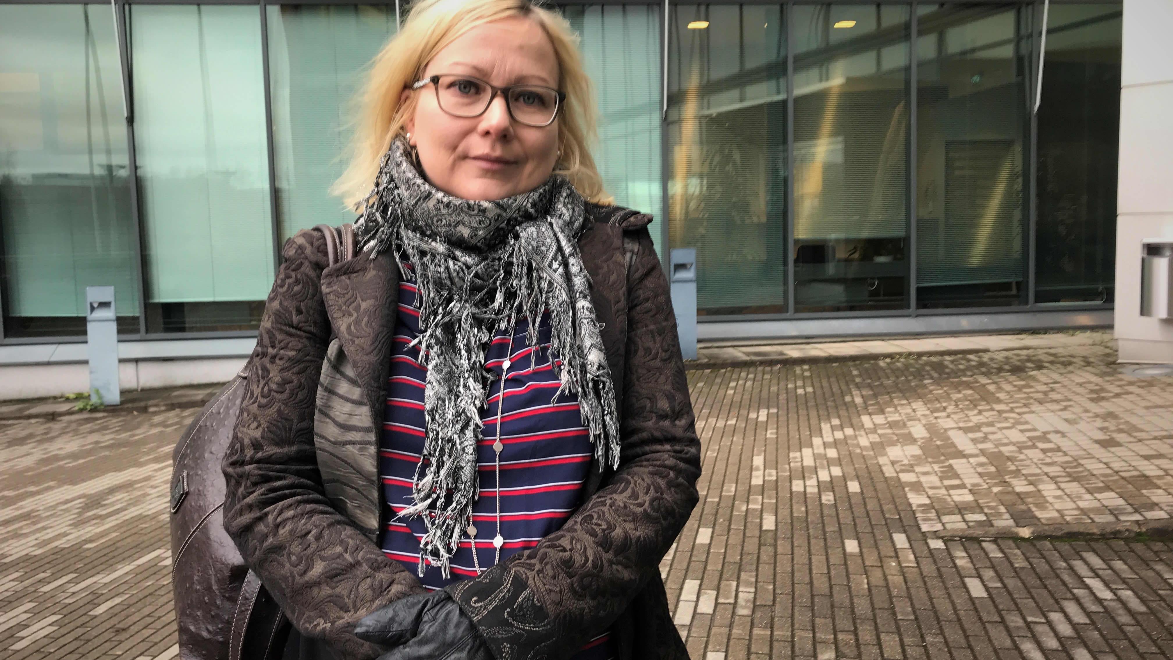 Ruskeatakkinen, vaaleahiuksinen nainen rakennuksen edessä.