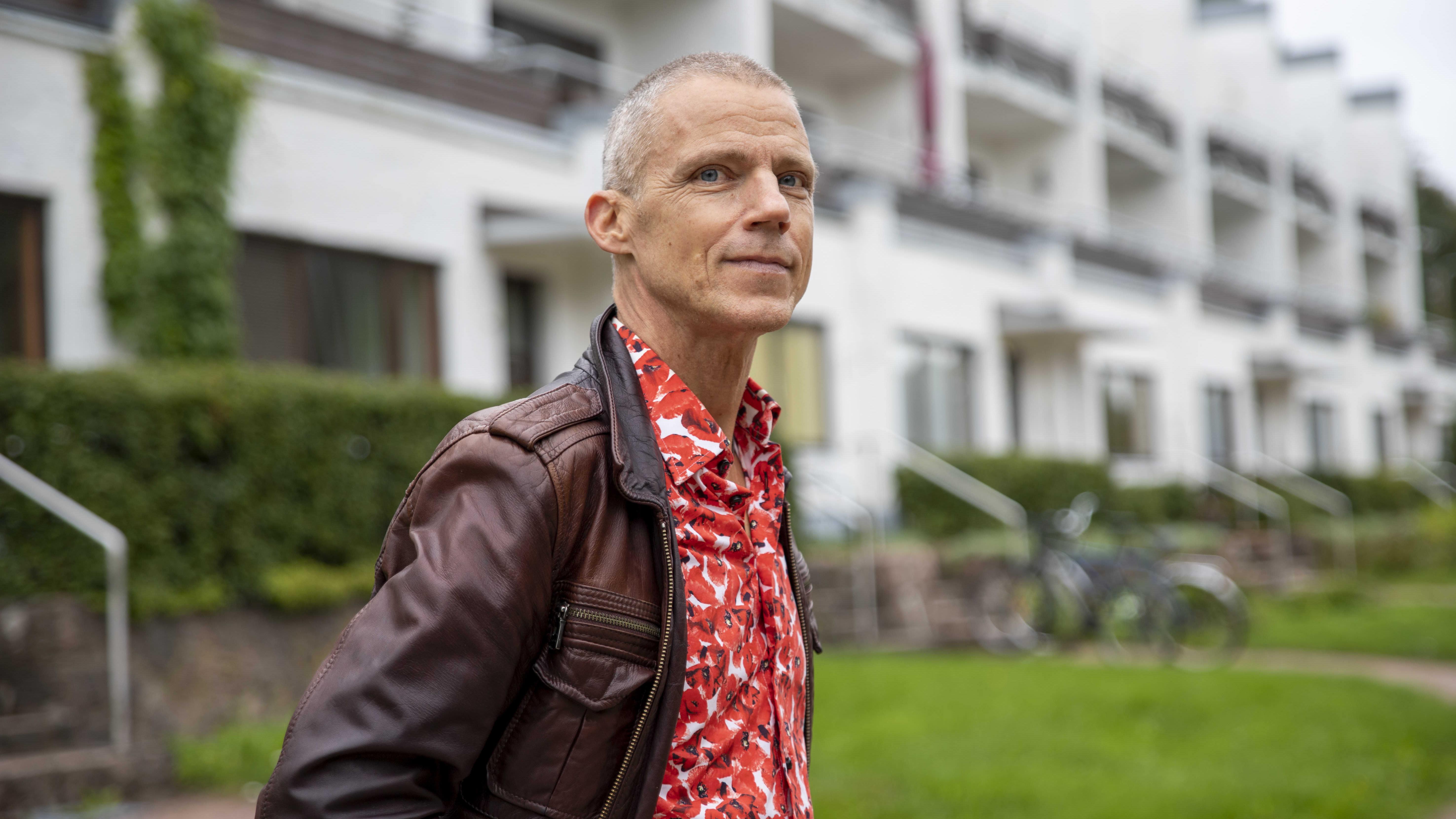 kirjailija Jari Järvelä poseeraa Kotkan Sunilan terassitalojen edustalla