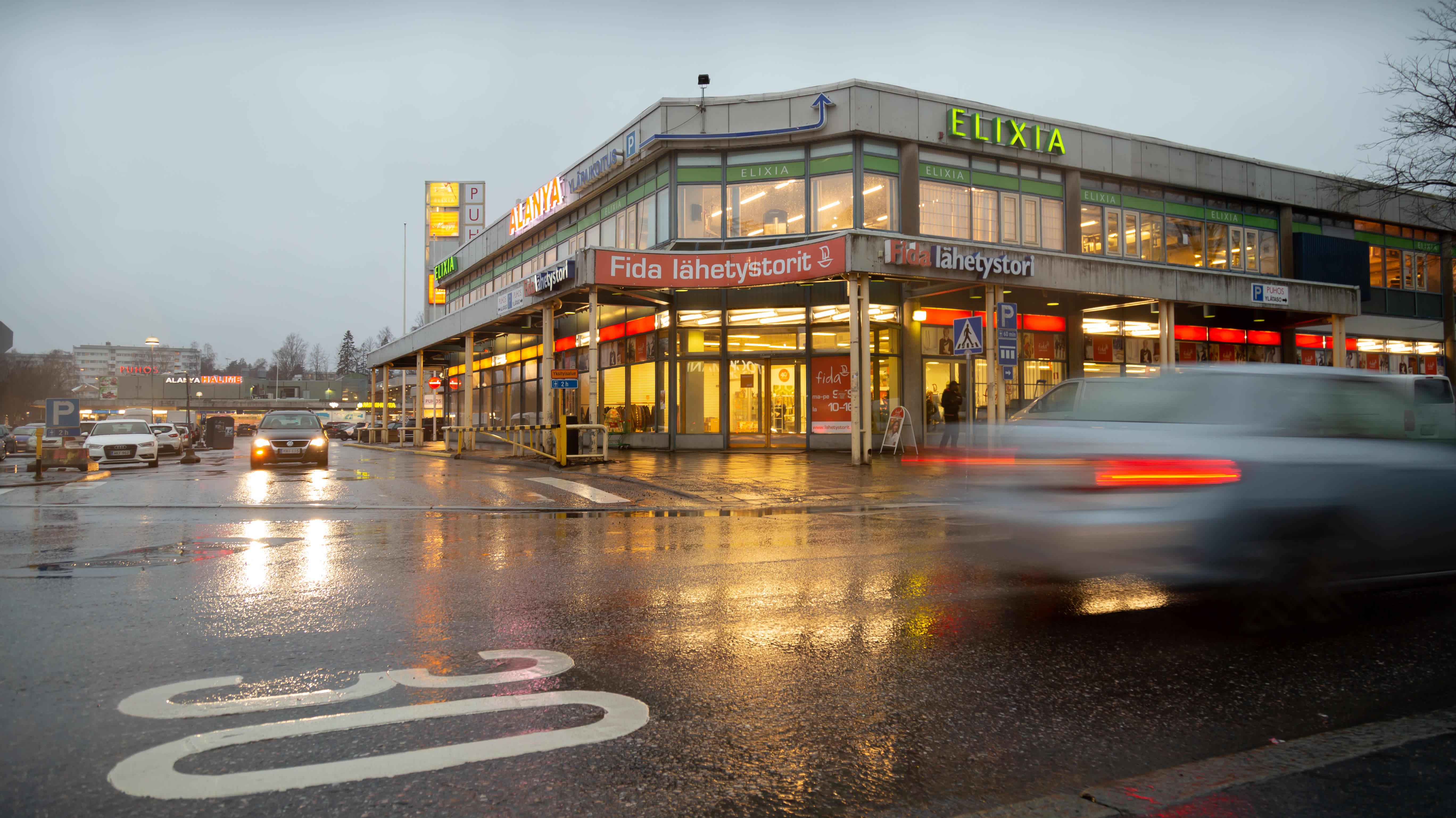 Kauppakeskus Puhos ulkoa päin. Eri liikkeiden valot loistavat sisältä lämpimästi sateisena päivänä. Liikeiden logoja: Fida, Elixia.  Auto hurahtaa juuri ohi, parkkipaikalta tulevan auton valot heijastuvat märästä asfaltista.