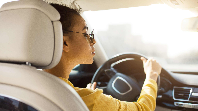 En kvinna kör bil. Hon är fotograferad bakifrån från baksätet.