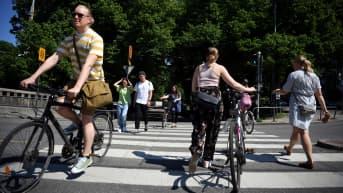 Kävelijöitä ja pyöräilijöitä suojatiellä.