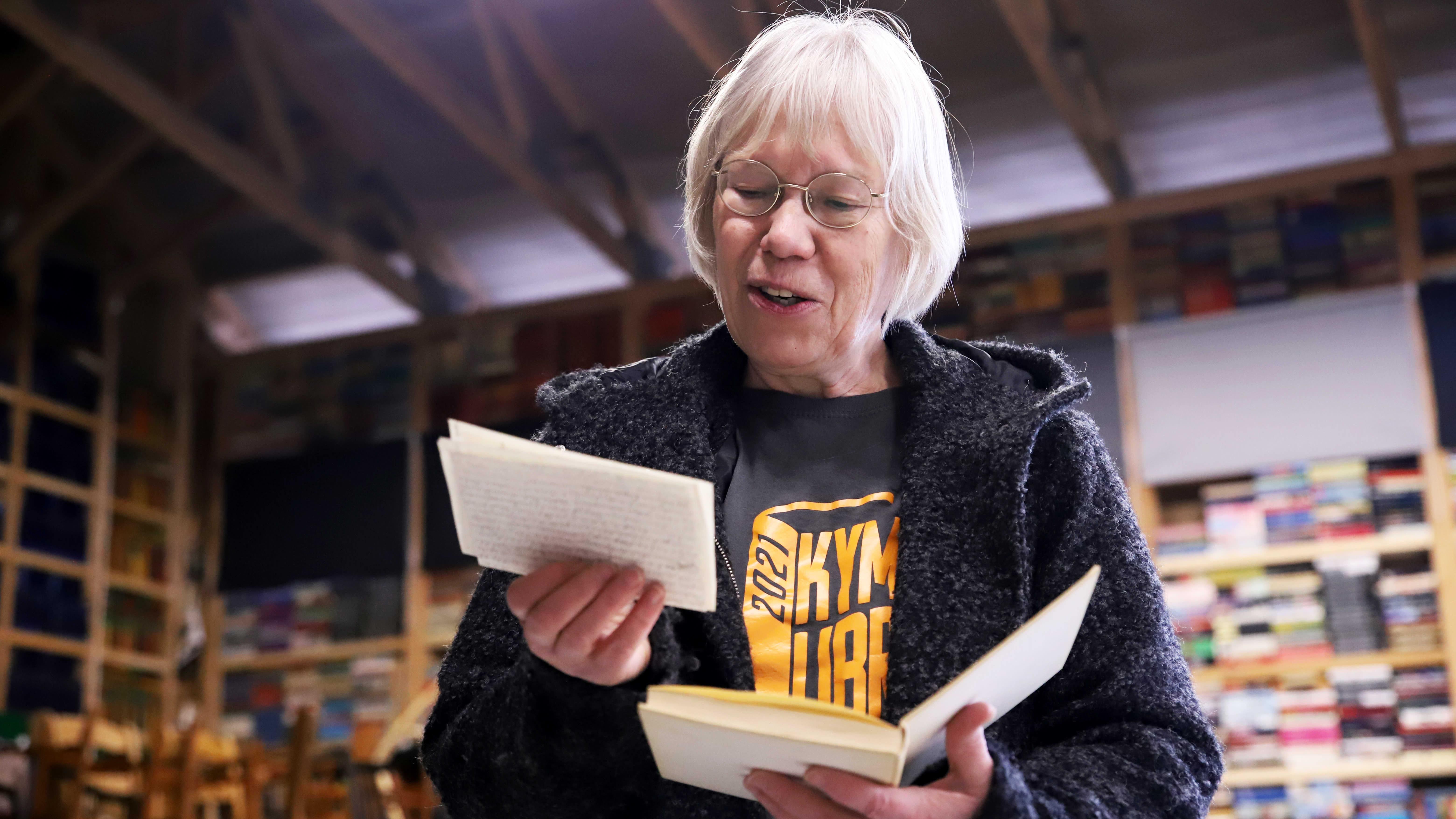 Tarja Tornaeus katselee käsissään olevan kirjan välistä löytynyttä kirjettä