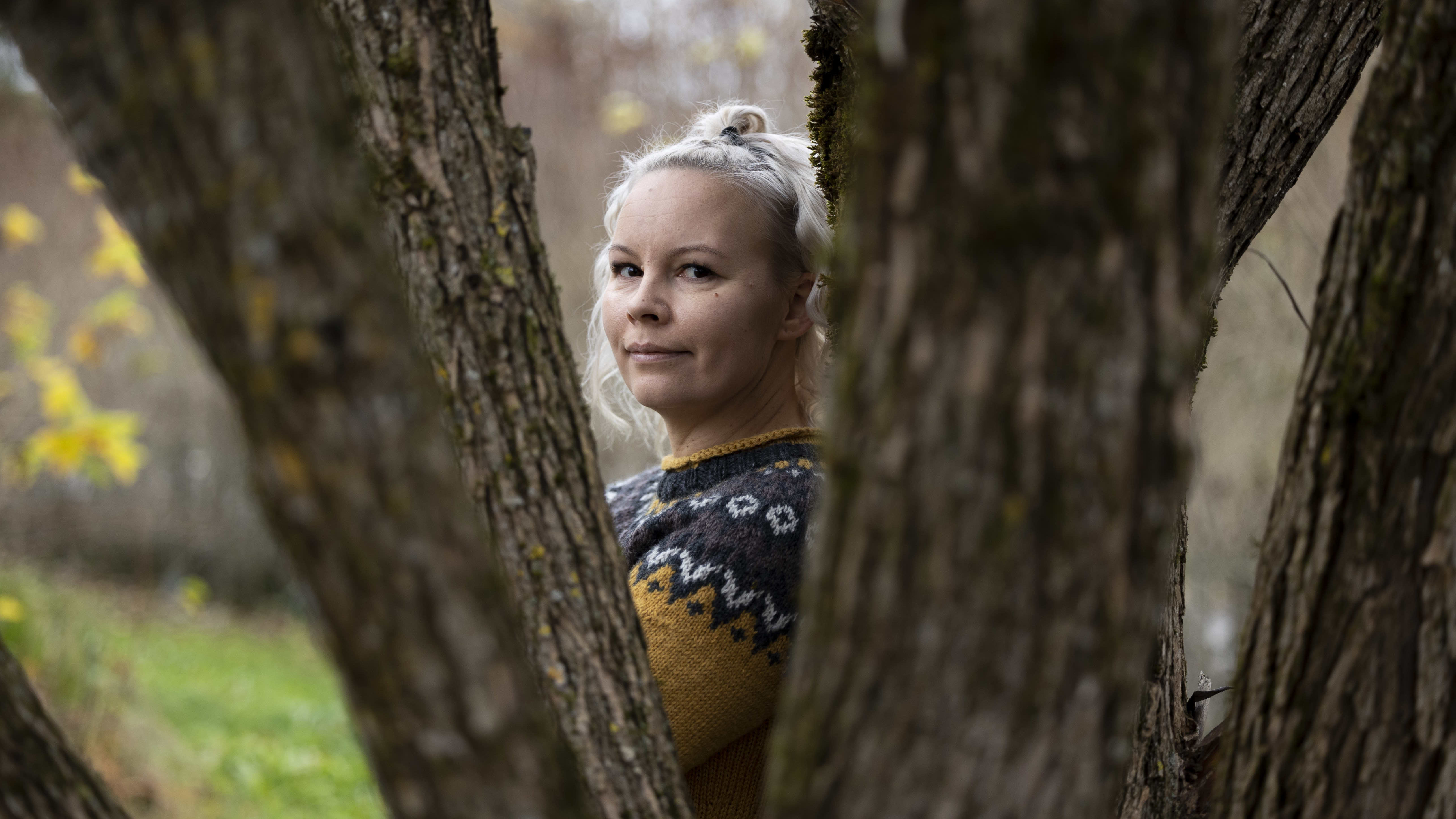 Potrettikuva vaaleahiuksisesta naisesta, joka seisoo sivuitse kameraan ja katsoo kameraan puiden takaa.