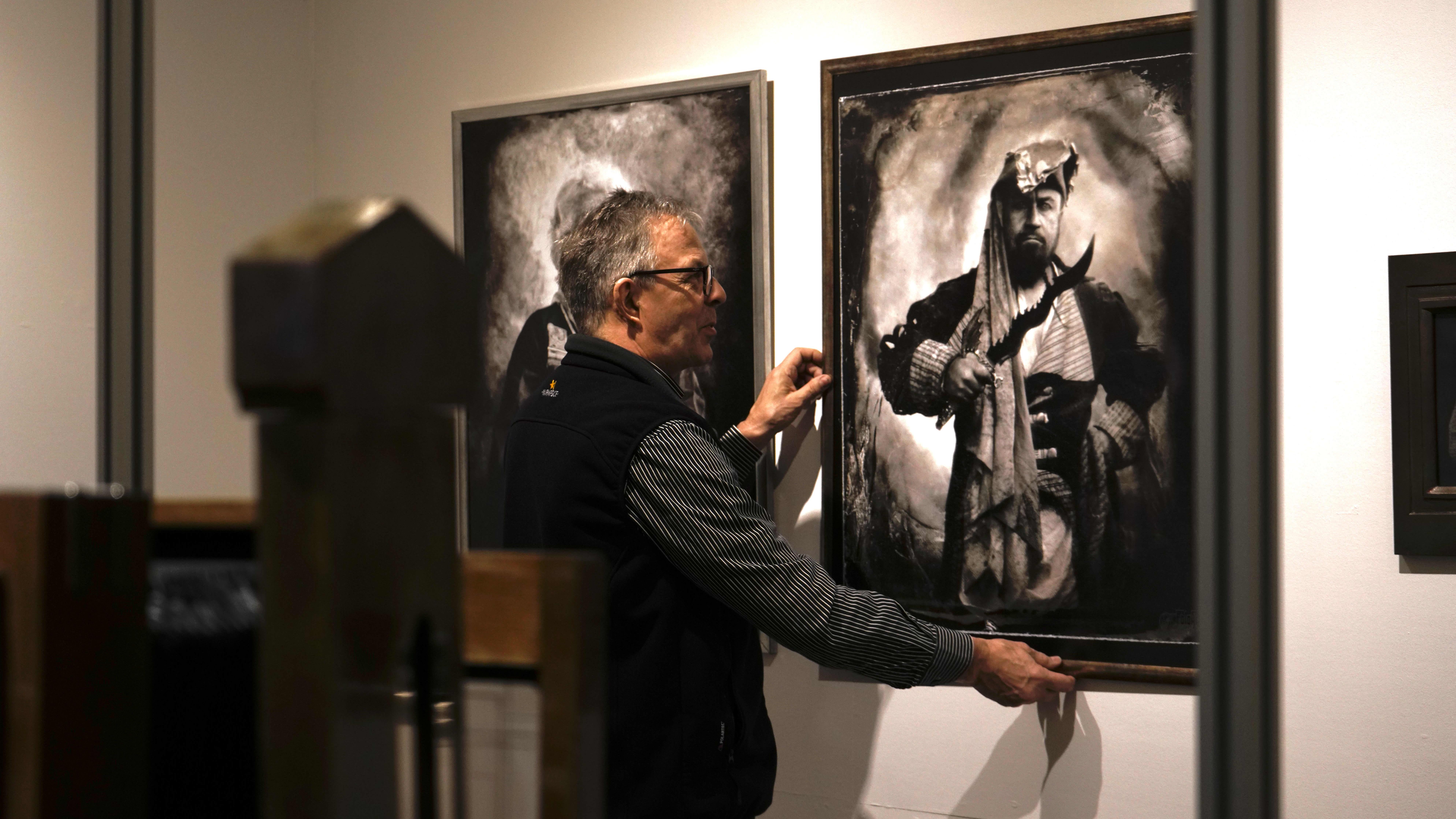 Pekka Homanen asettelee kehystettyjä kuvia esille Kainuun museolla.