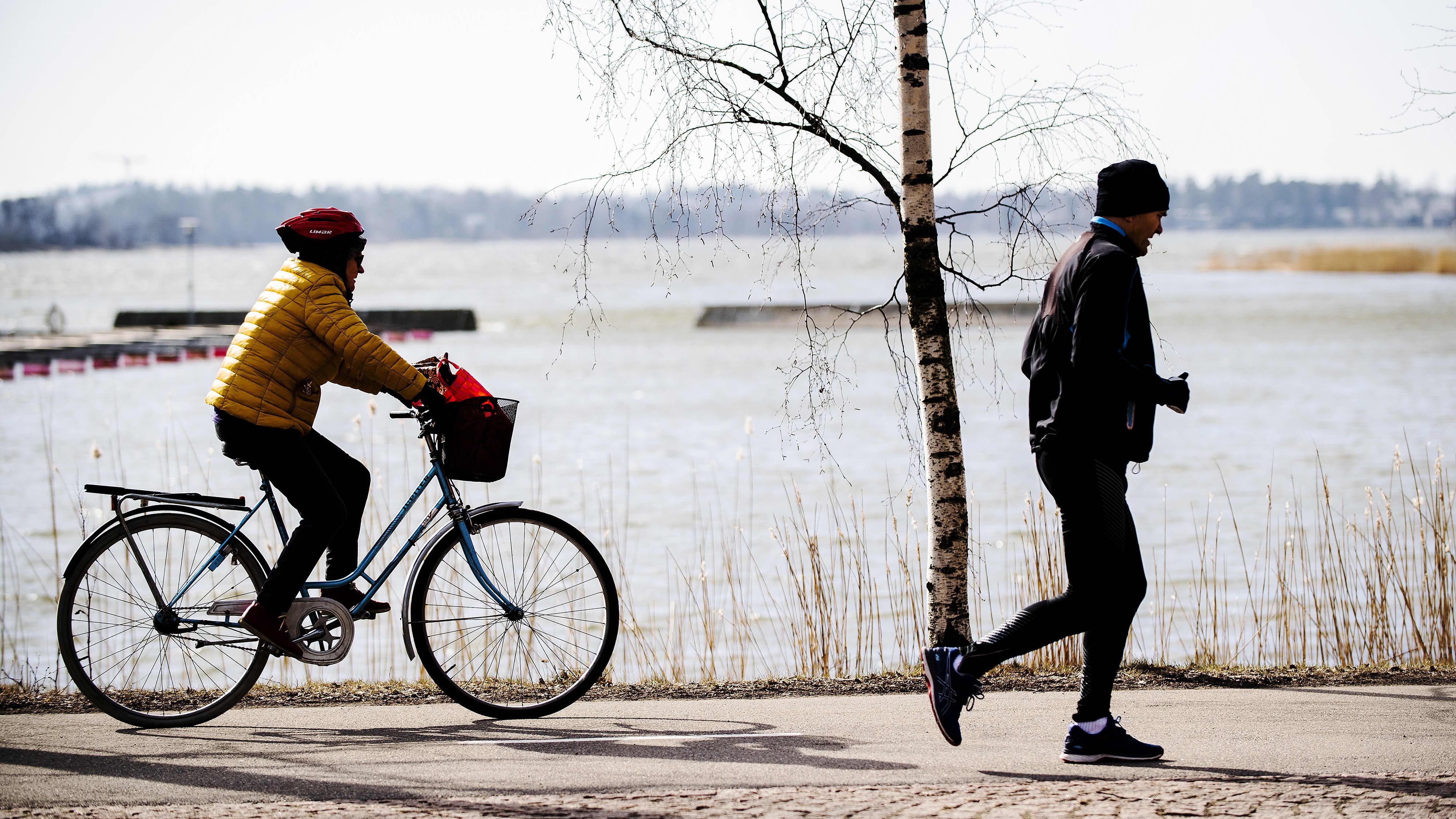 Kuvassa on pyöräilijä ja juoksija meren rannassa.