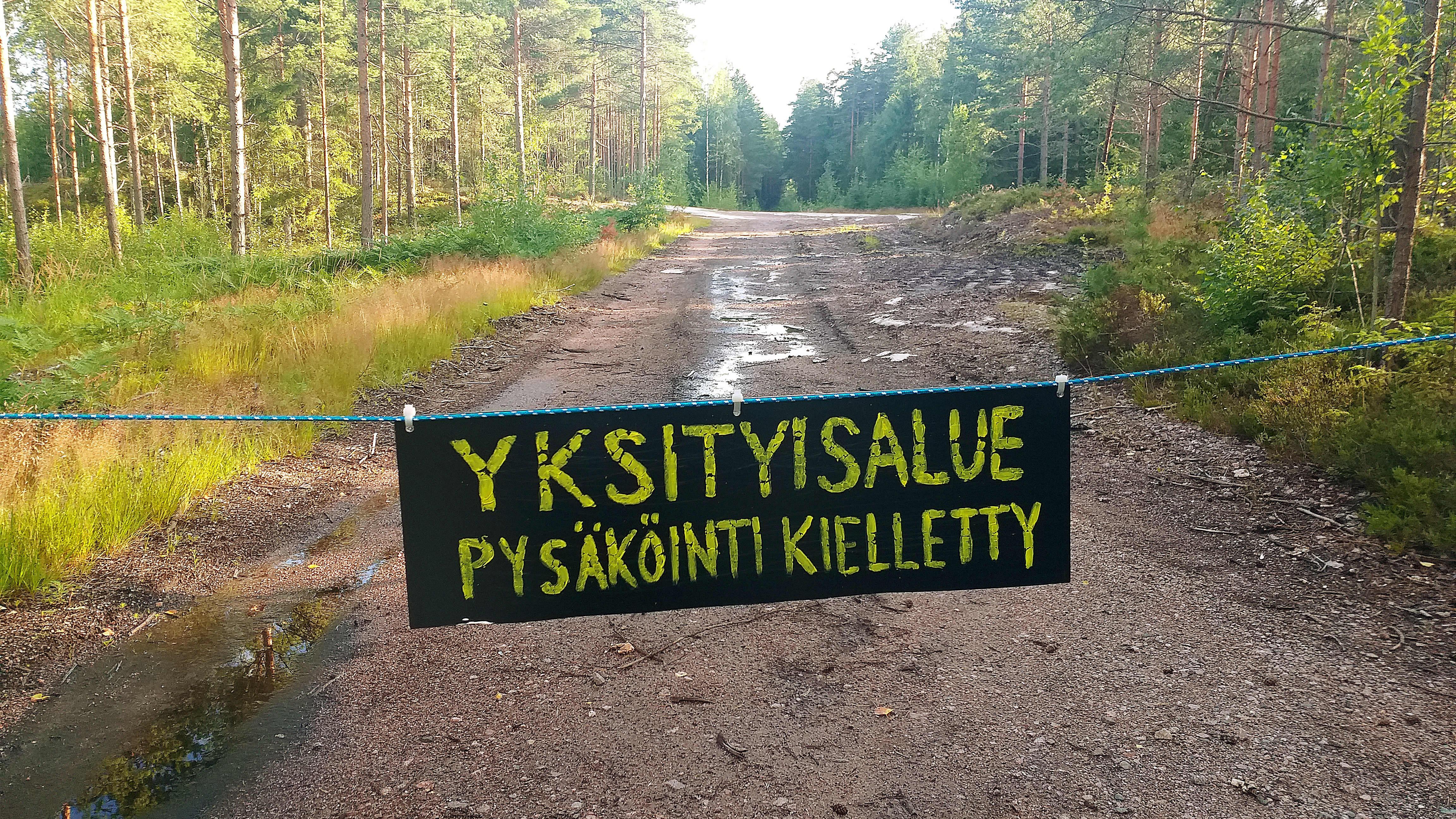 Yksityisalue – pysäköinti kielletty -kyltti yksityistiellä metsän keskellä