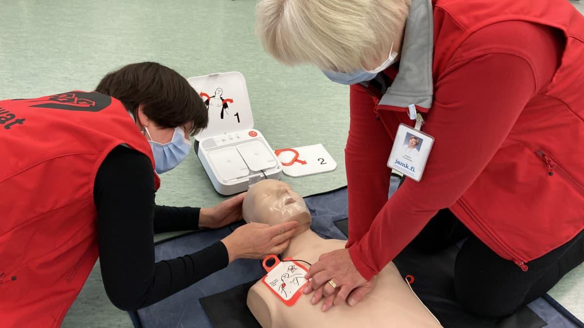 Kaksi naista elvyttää harjoittelunukkea sydäniskurilla.