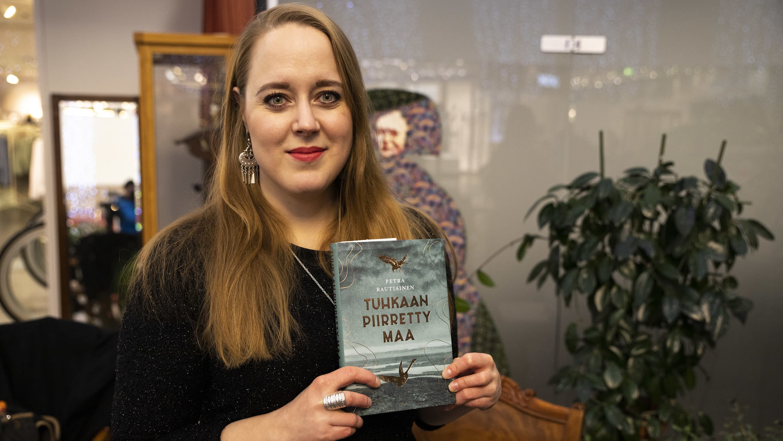 Kirjailija Petra Rautiainen kädessään hänen Savonia-palkittu esikoisteoksensa Tuhkaan piirretty maa.