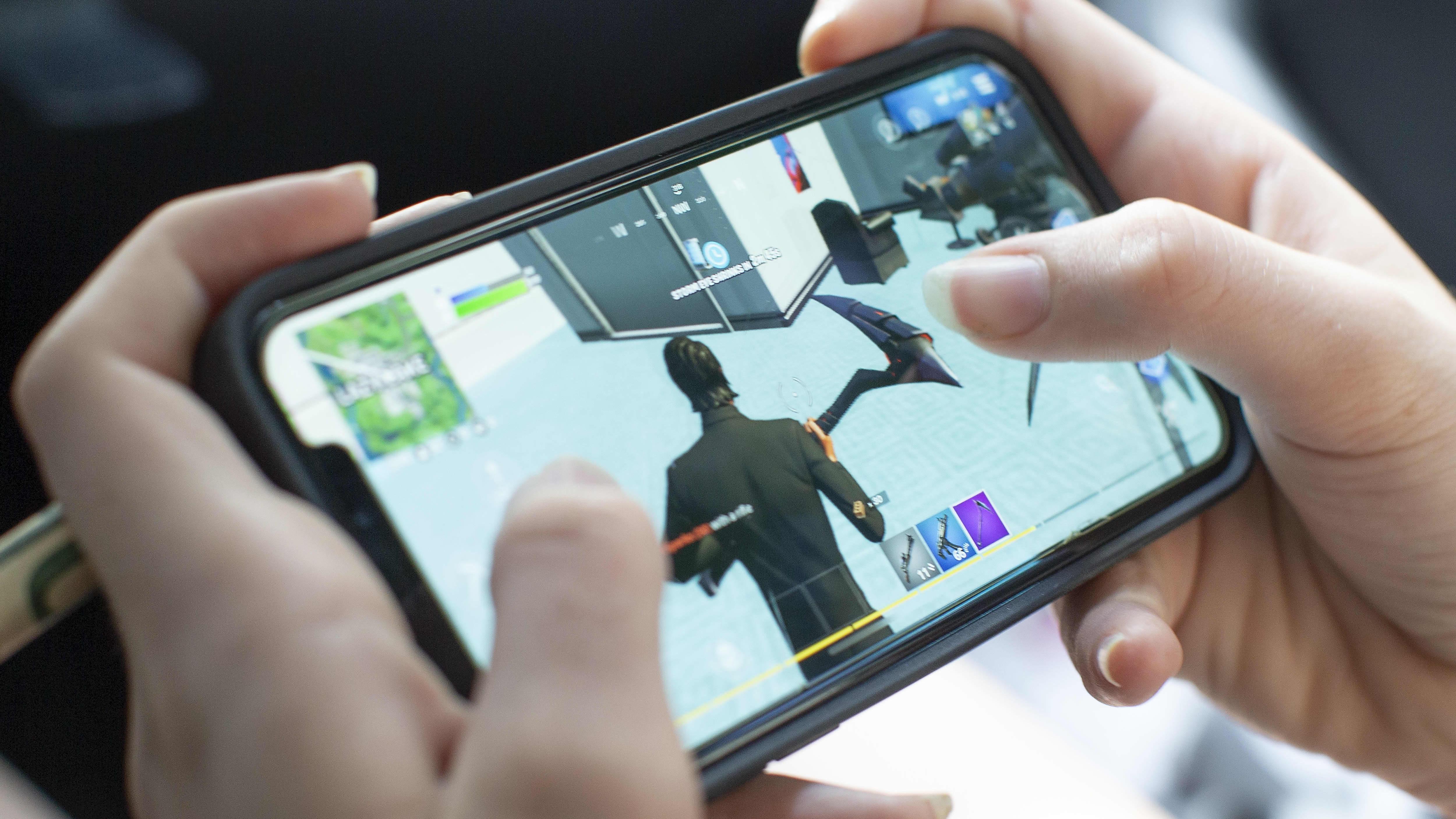 En tonåring spelar Fortnite på en Applemobil i Billerica i USA-delstaten Massachusetts den 24 augusti 2020.