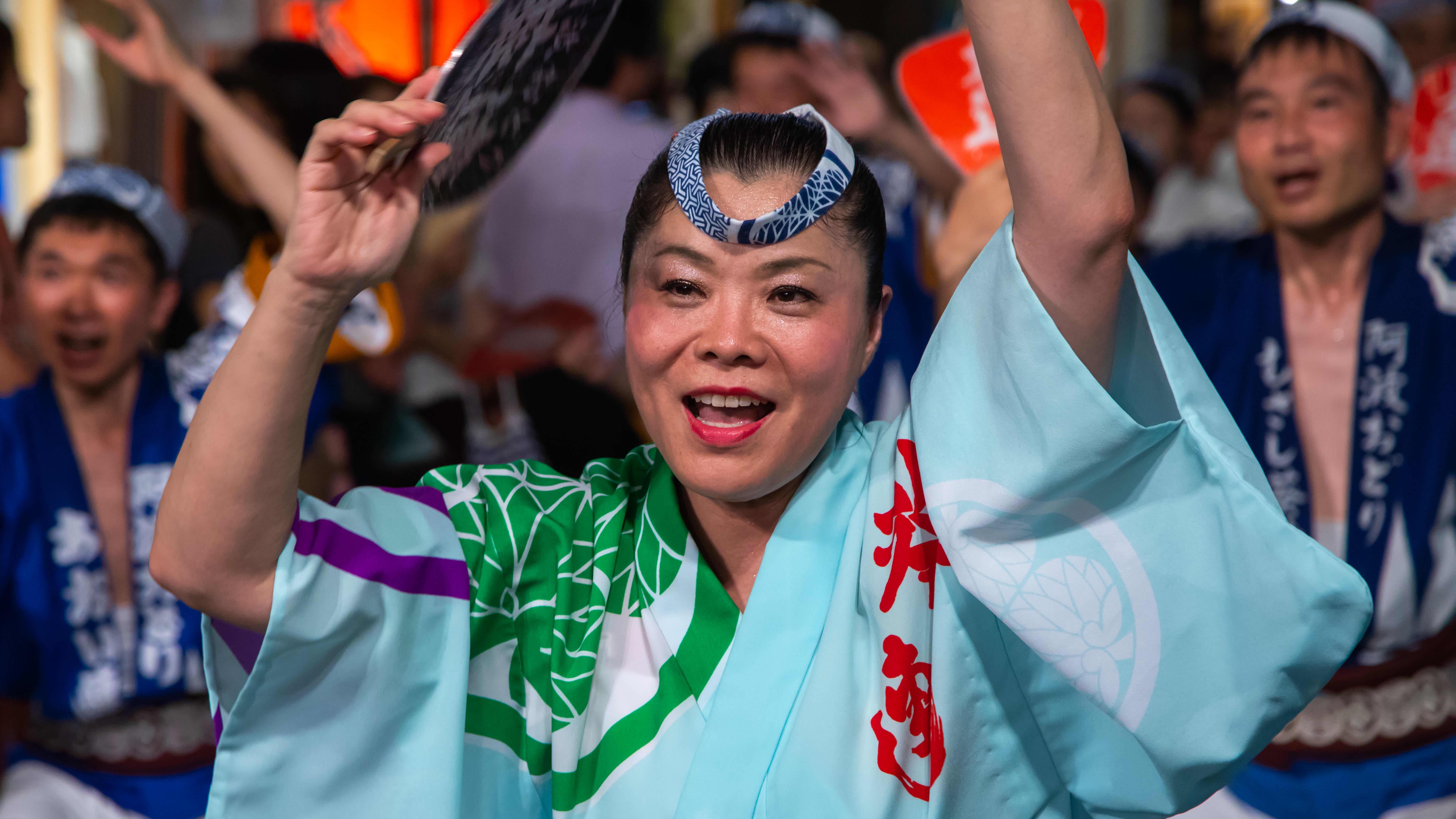 Yukata-asuun pukeutunut nainen juhlii festivaalilla Japanissa.