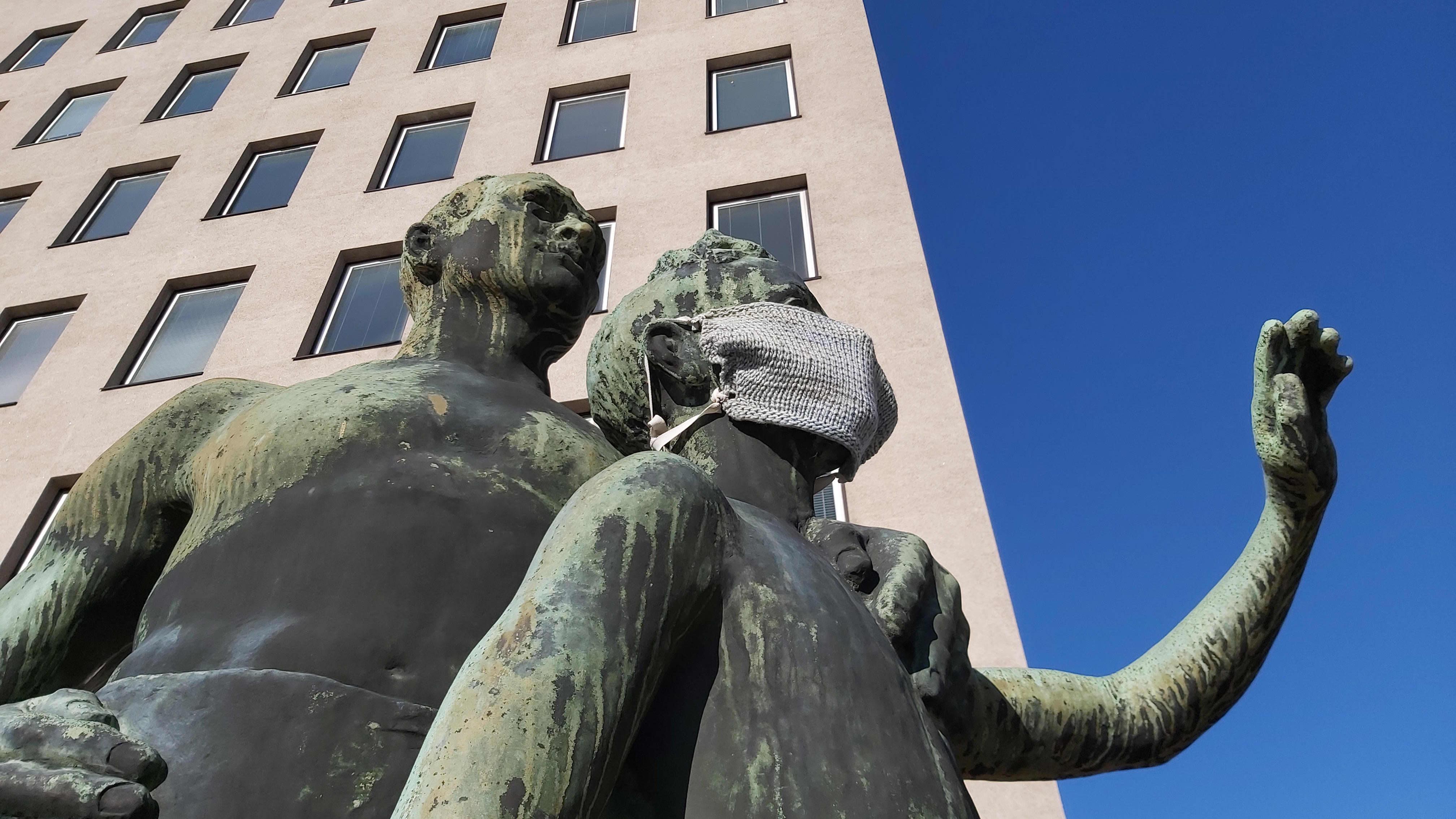 Kuva Kotkan kaupungintalolta patsaasta, jossa on mies ja lapsi. Lapsipatsaan kasvoilla on neulottu kasvomaski.