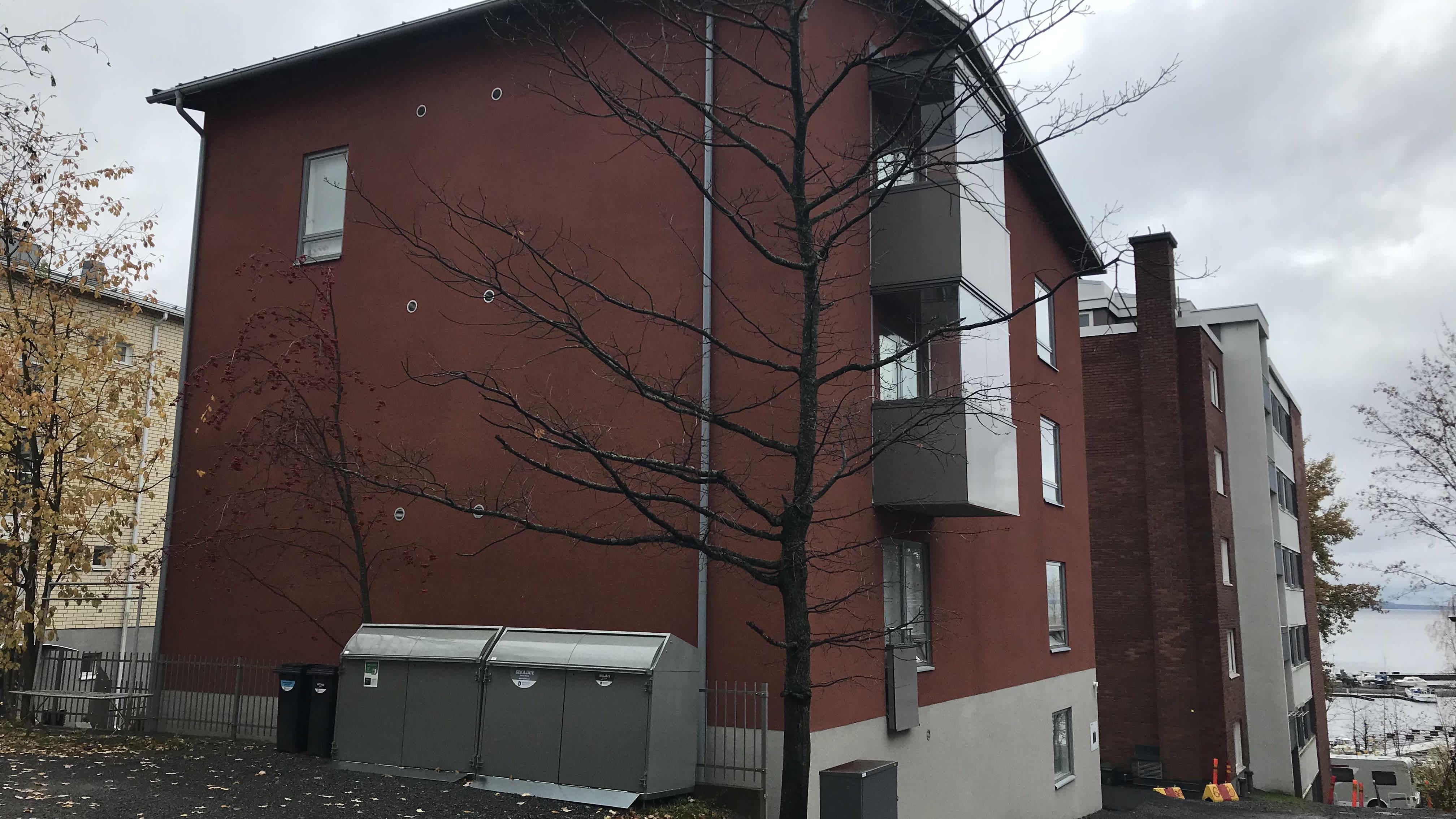 Punainen pienkerrostaloa Tampereen Armonkalliolla. Talon takana näkyy vanhempi punatiilinen kerrostalo ja Näsijärveä.
