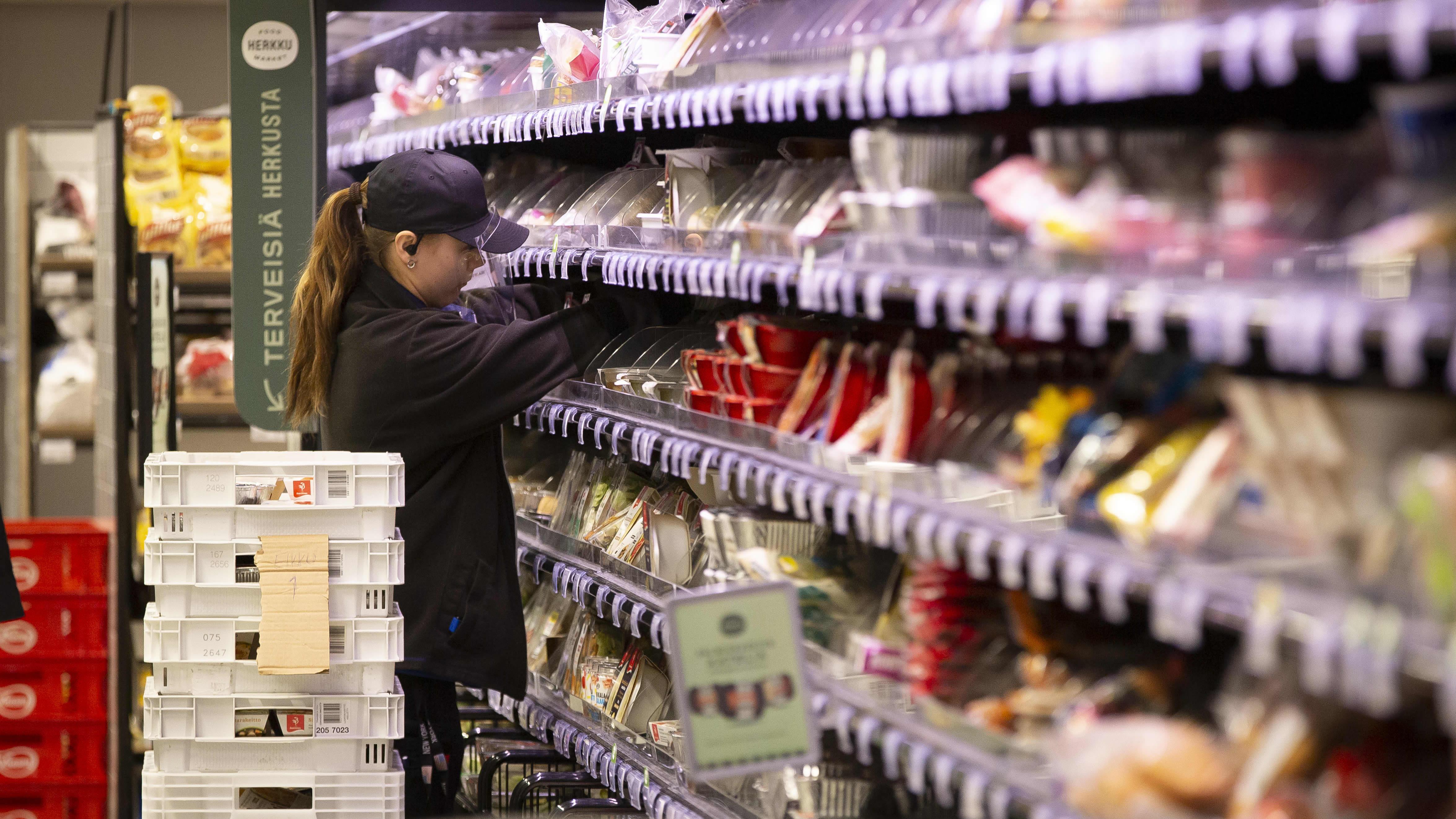 Kaupanmyyjä laittaa tuotteita hyllyyn S-market Vallilassa.