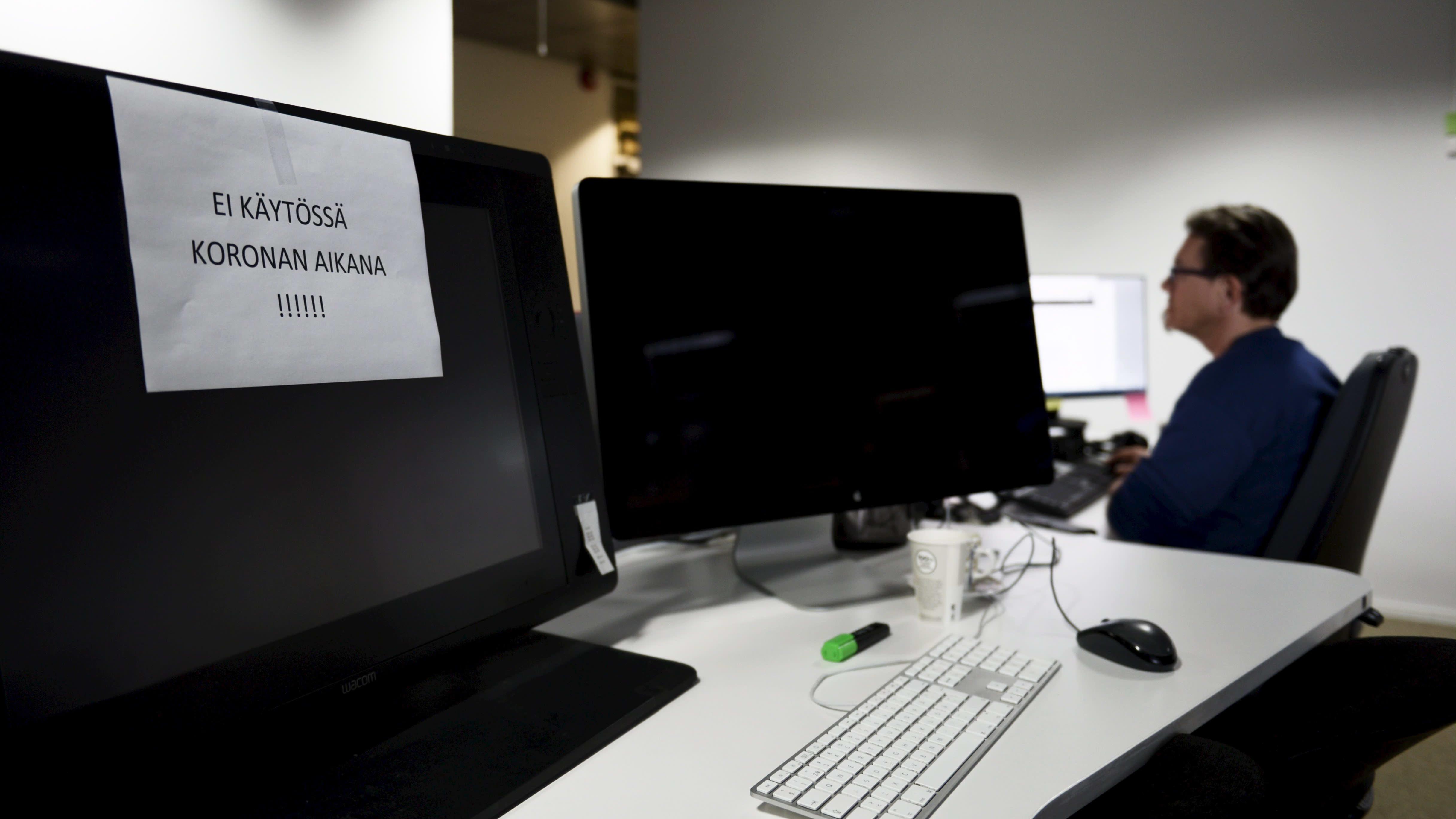Ei käytössä koronan aikana -lappu tietokoneen näytöllä toimistossa Helsingissä 28. toukokuuta 2020.