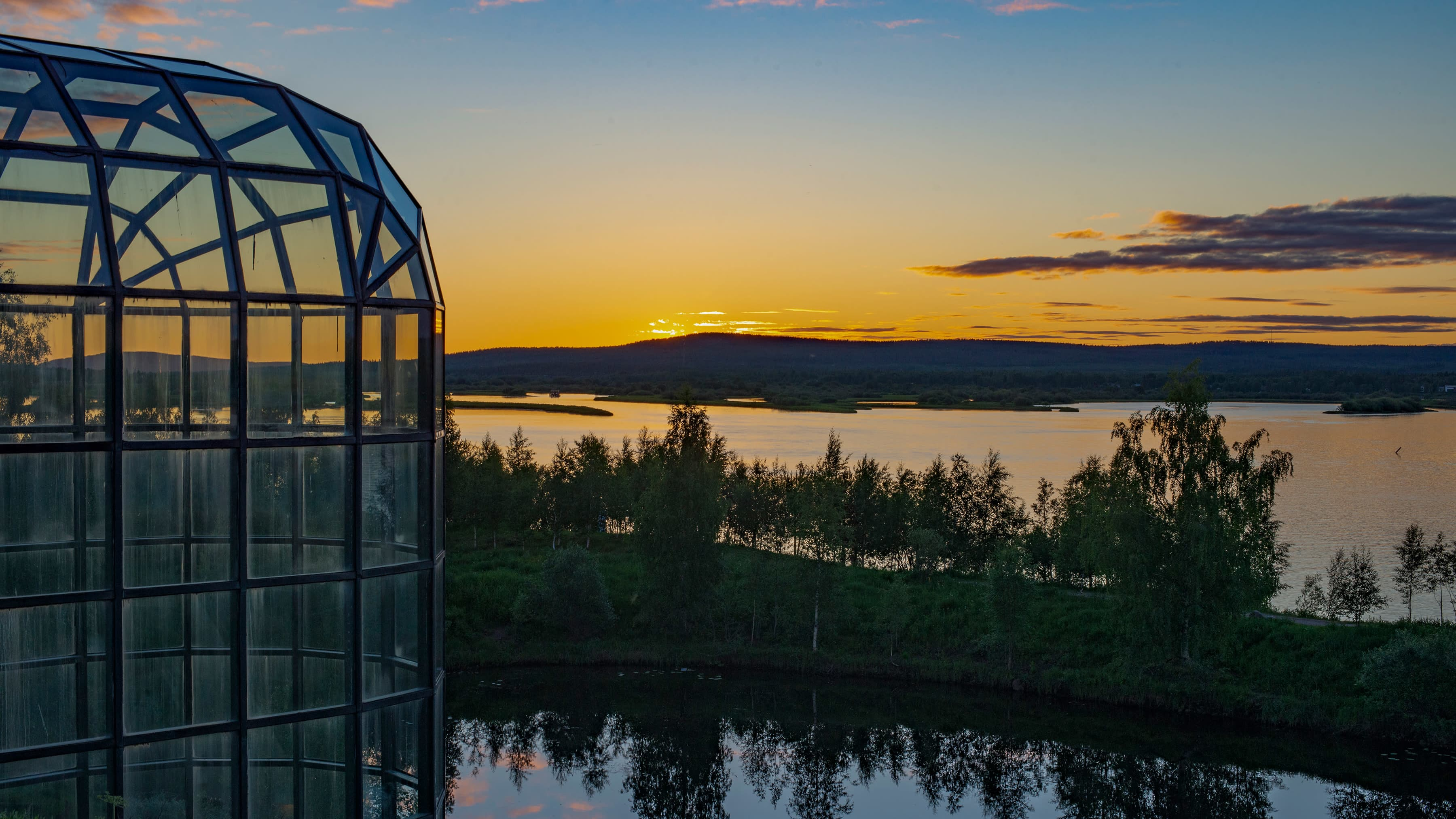 Keskiyön aurinko laskee Ounasjoen taakse, etualalla Arktikum-talon lasikattoa.