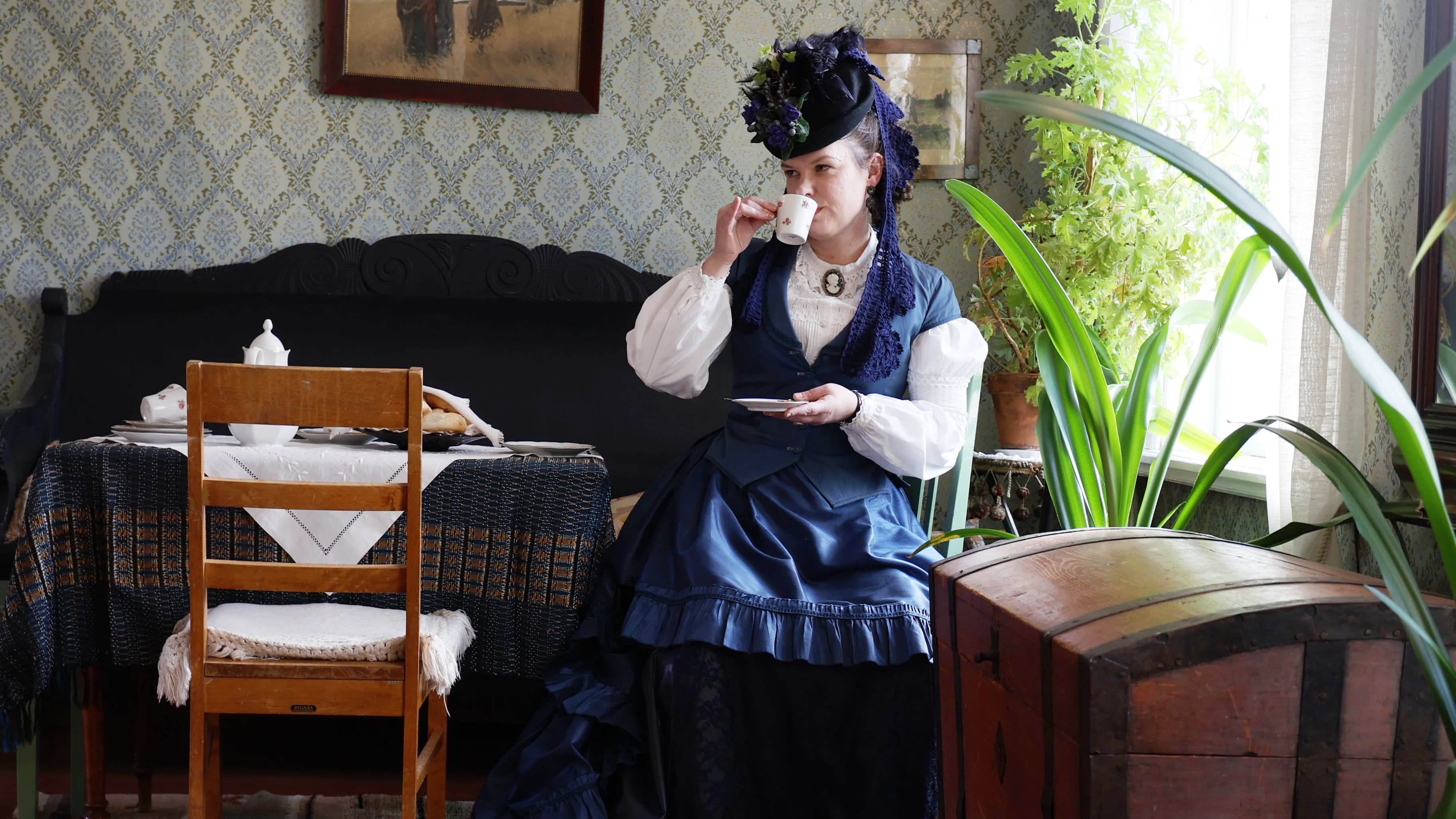 Taina Parikka juo teetä 1880-luvun henkinen leninki ja koristeellinen hattu yllään. Hän istuu Haminan Kauppiaantalomuseon salissa teepöydän äärellä. Huonekalut, tapetit ja taulut ovat 1800-luvun lopun tyyliä.