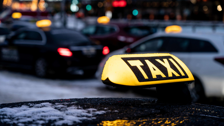 Taksikyltti auton katolla, taustalla muita takseja.