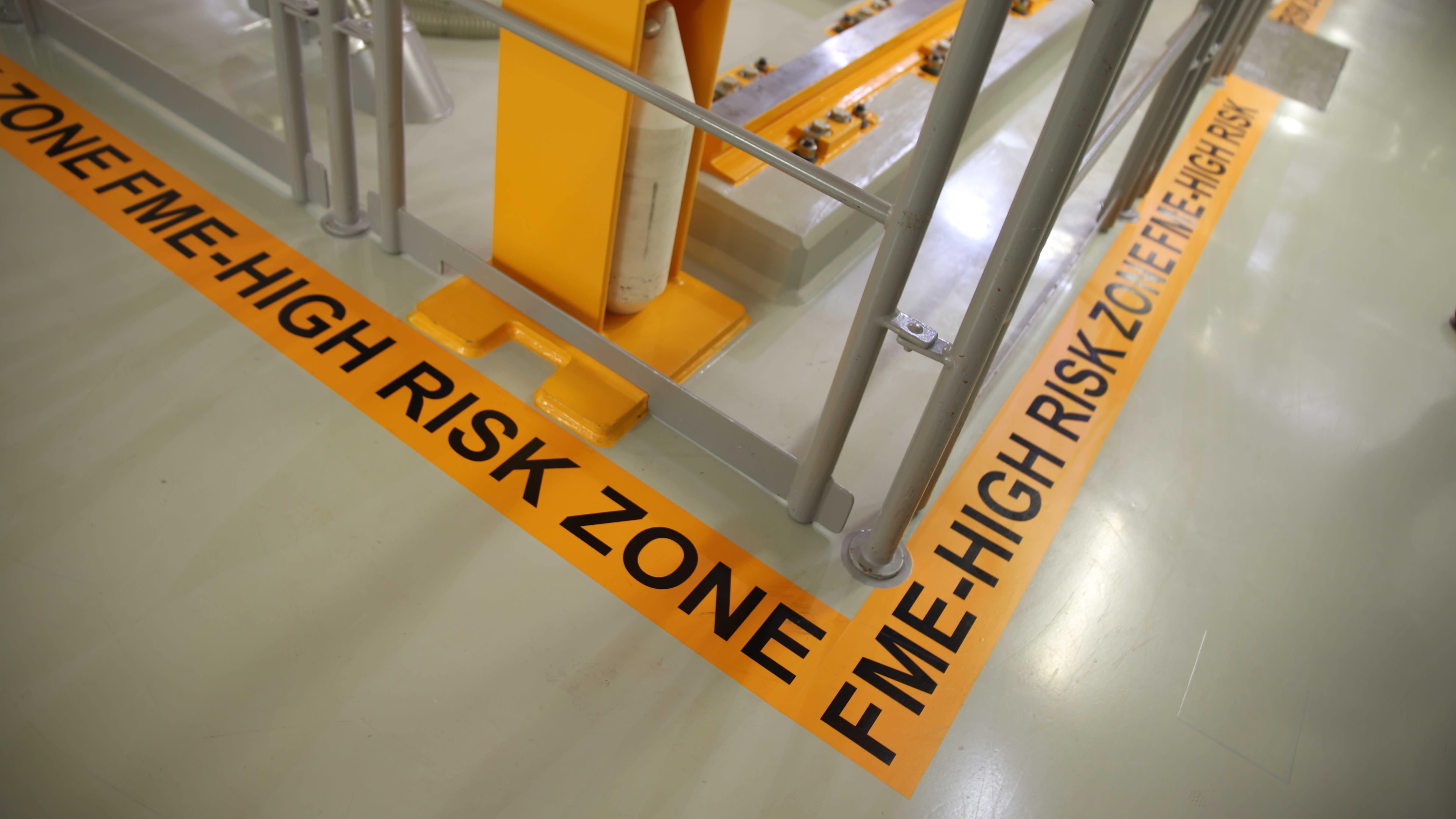 """Reaktoriallasta kiertää oranssi """"FME High Risk Zone"""" -teksti, jolla pyritään varoittamaan ulkopuolisen materiaalin kulkeutumisesta altaaseen."""