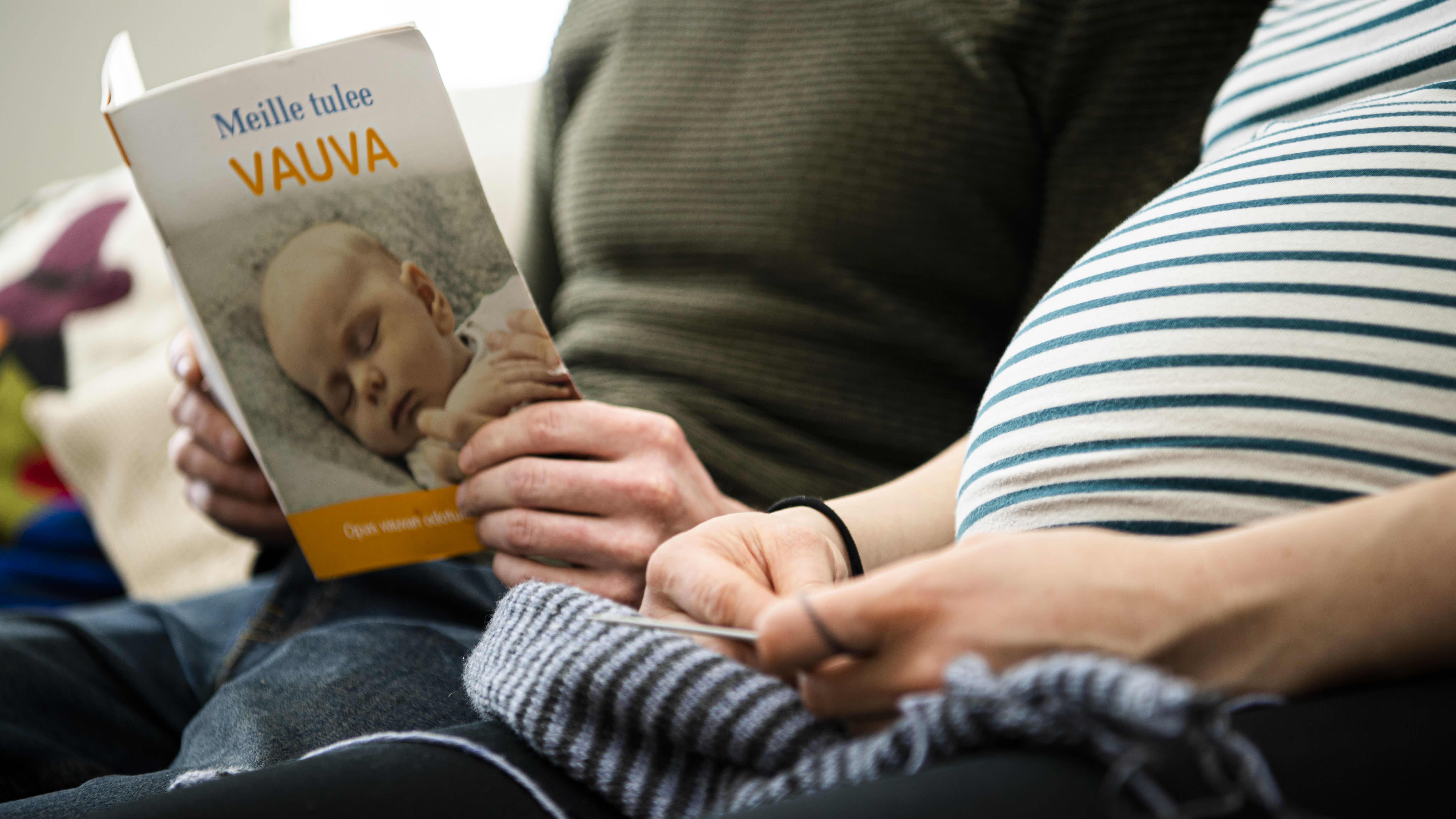 """Raskaan olevan henkilö lukee kumppaninsa kanssa """"Meille tulee vauva"""" kirjaa."""