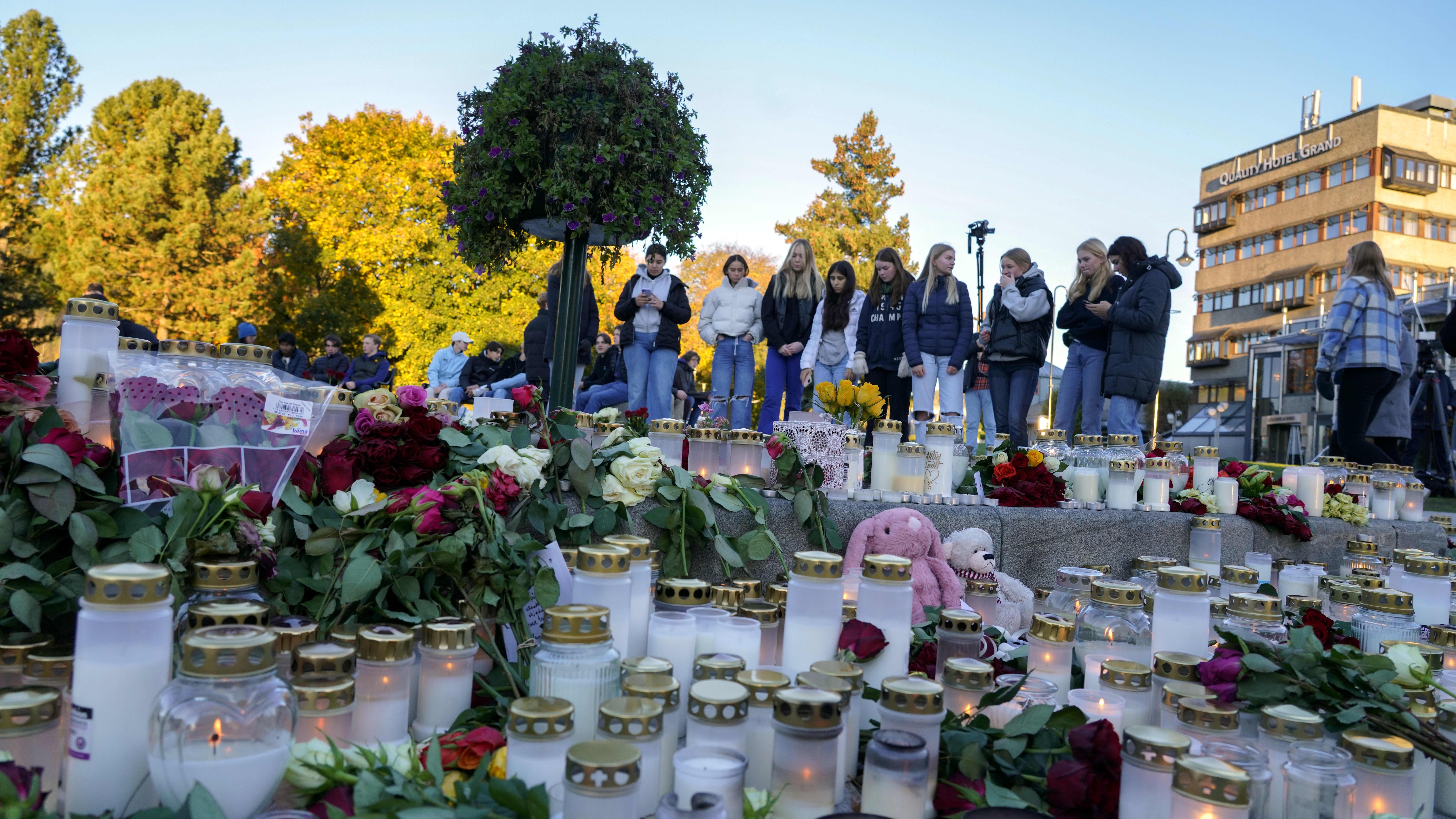 Människor står bakom en stor mängd gravljus och blommor. De ser ledsna ut.