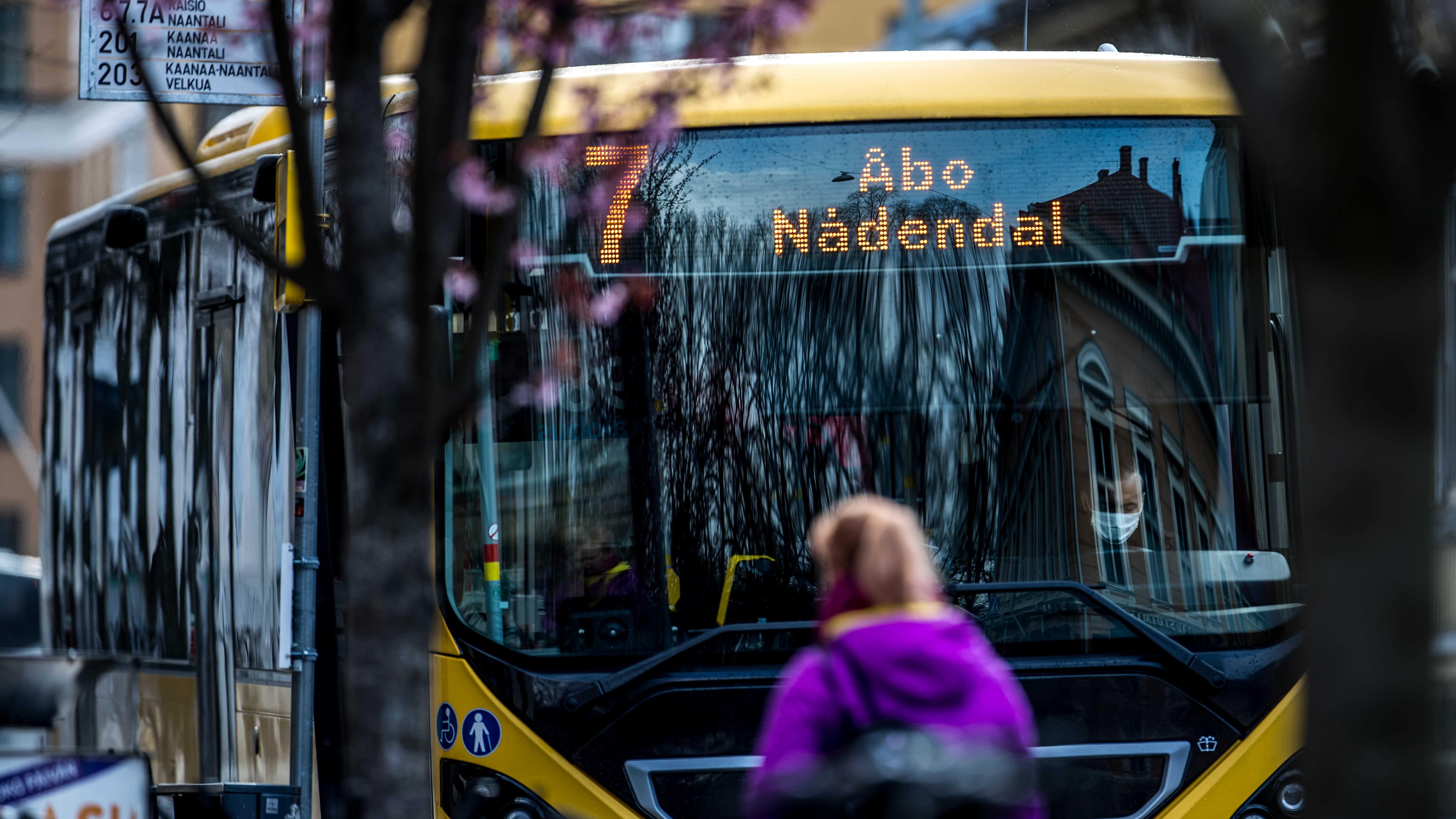 Fölin bussi ja matkustaja auton ulkopuolella.