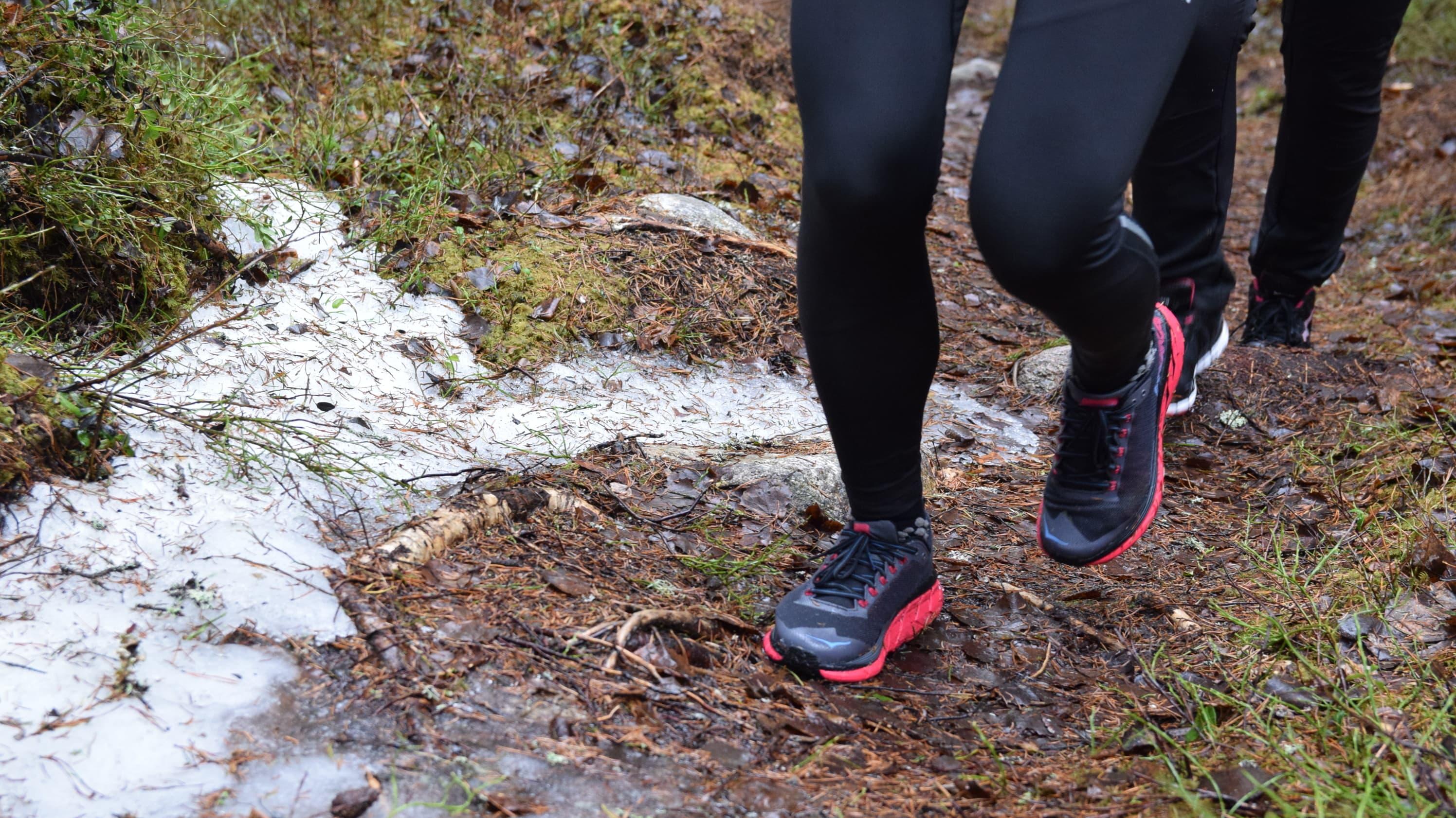 Närbild av fötter med gymnastikskor som pringer på en skogsstig med lite snö på.
