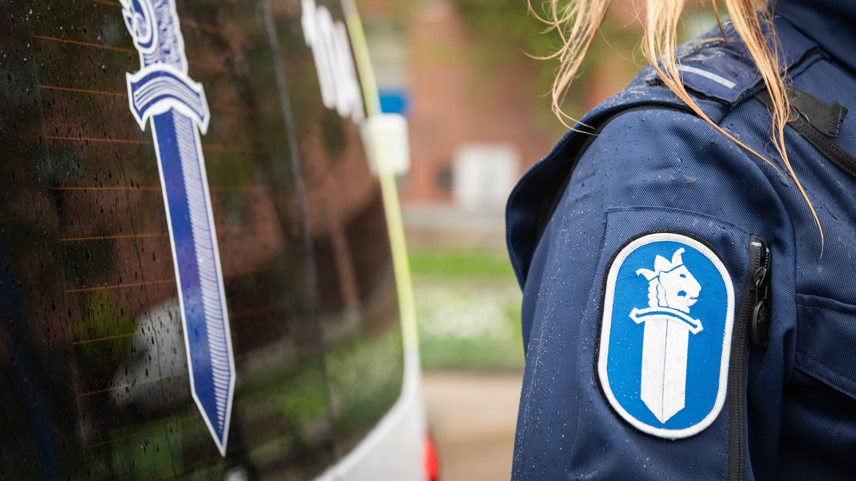 Hihamerkki auton vierelläseisovan poliisin haalarissa.