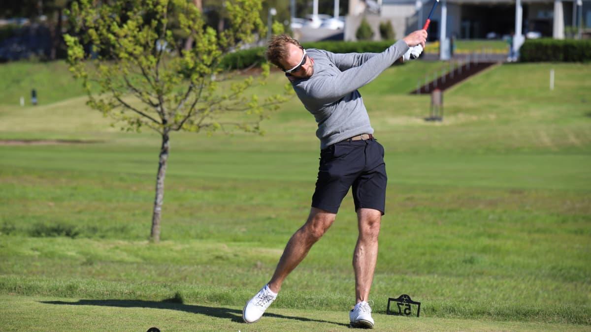 Mies lyö golfpalloa