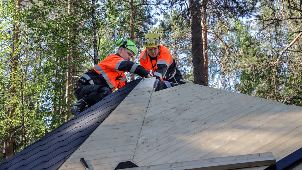 Rakennusmies Markus Parviainen ja Metsähallituksen suunnittelija Leo Parkkonen kodan katolla.