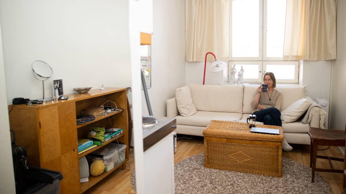 Saila Suominen istuu beigellä sohvalla juomassa teetä.