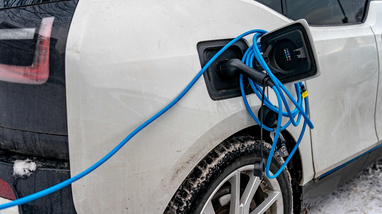 Sähköauton sininen latausjohto vyyhtinä auton latausluukun ympärillä.