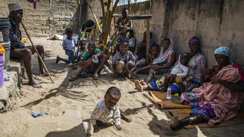 ryhmä ihmisiä istuu muurin varjossa Mosambikissä, etualalla pieni lapsi