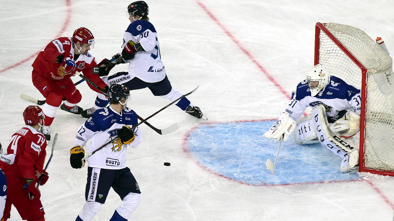 Suomen jääkiekkomaajoukkueen pelaajat puolustavat omaa maalia, kun venäläispelaajat hyökkäävät.
