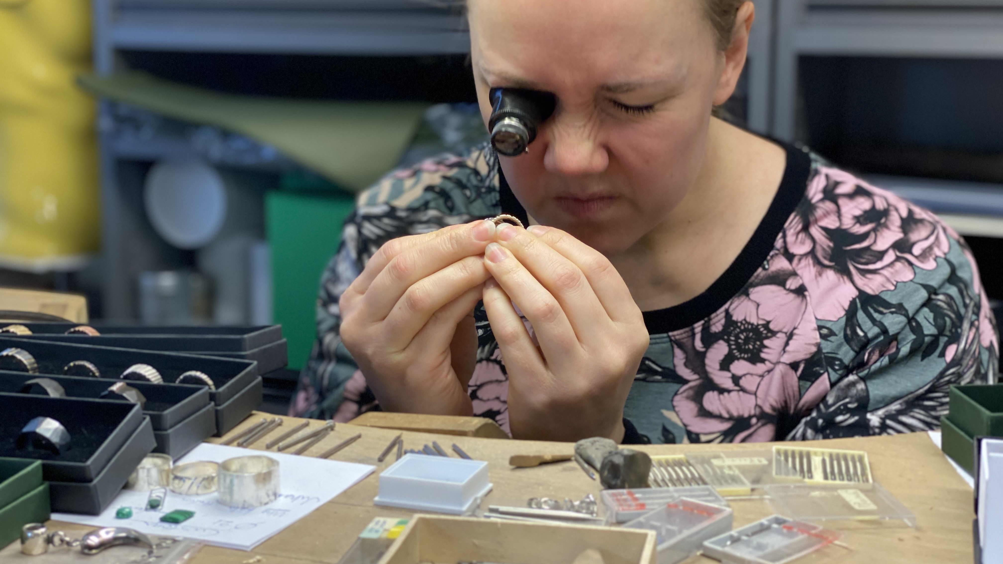 Jenni Rutonen tutkii sormusta luupilla.