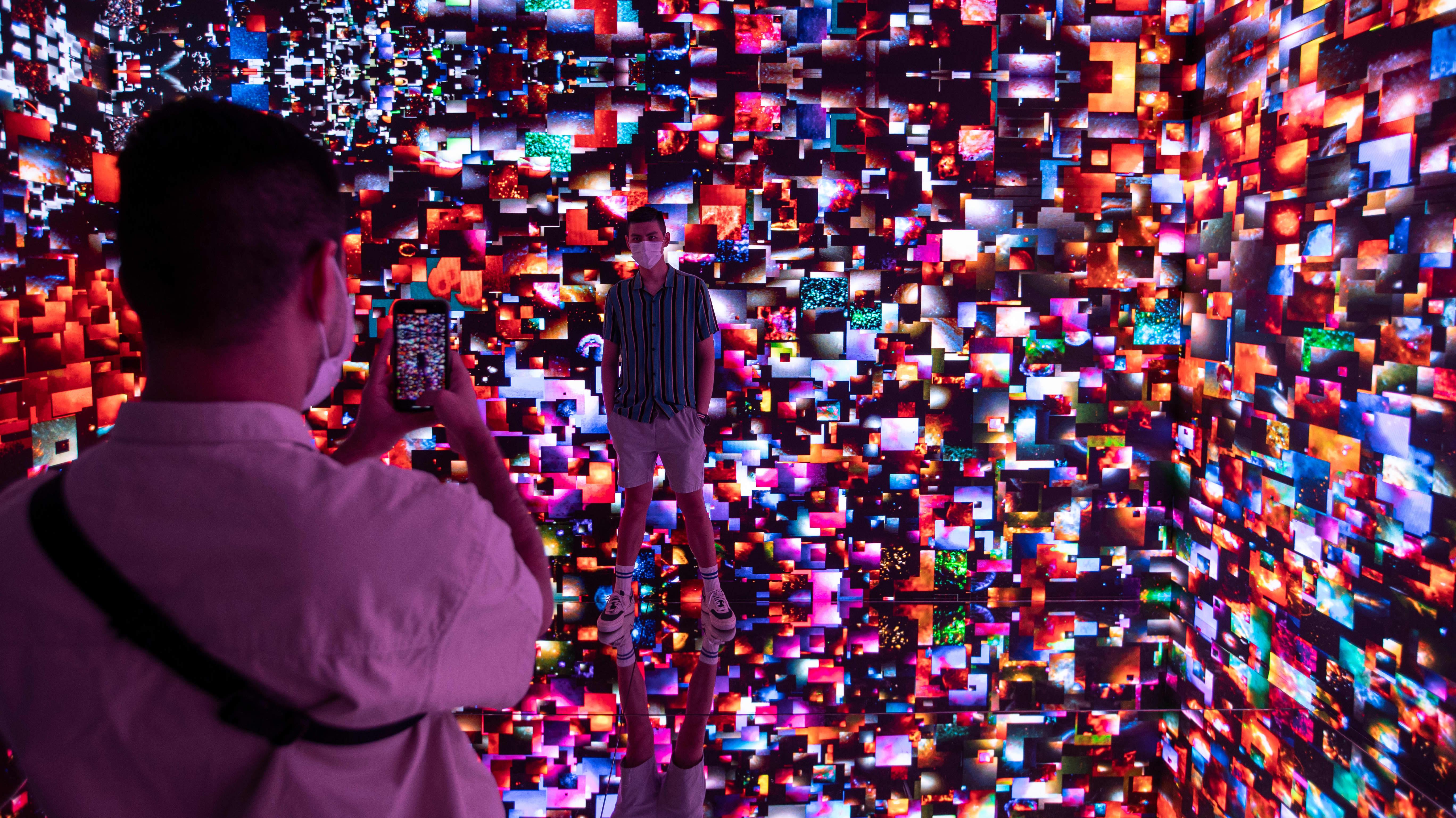 Ihmiset ottivat kuvia Refik Anadolin Machine Hallucination Space: Metaverse Lot 1 -digitaideteoksessa.
