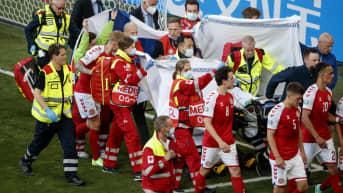 Tanskan Kööpenhaminan Parkenin hoitohenkilökunta viemässä Christian Erikseniä pois.