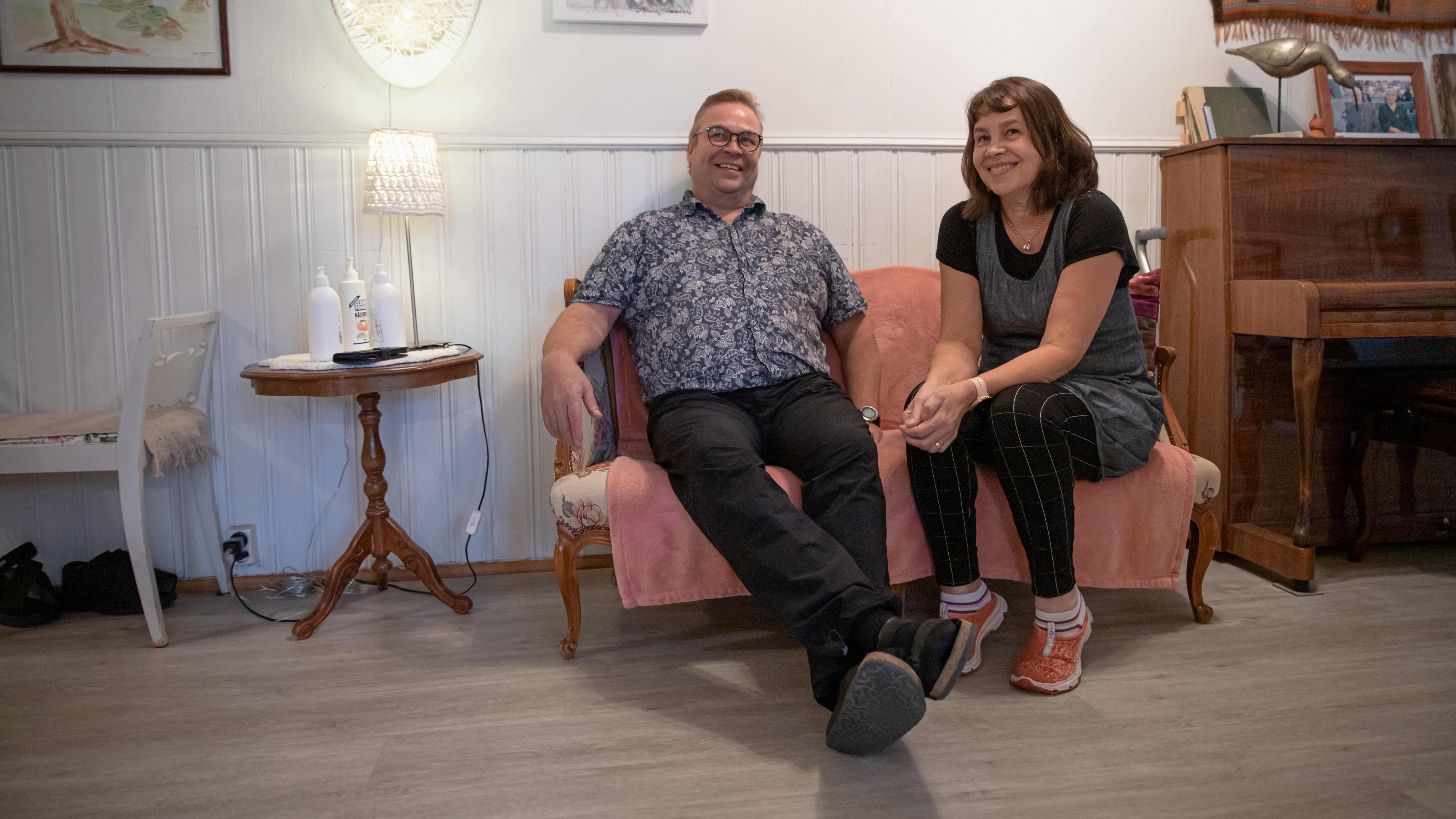 Ari ja Soili Kalliokoski hymyilevät istuessaan sohvalla.