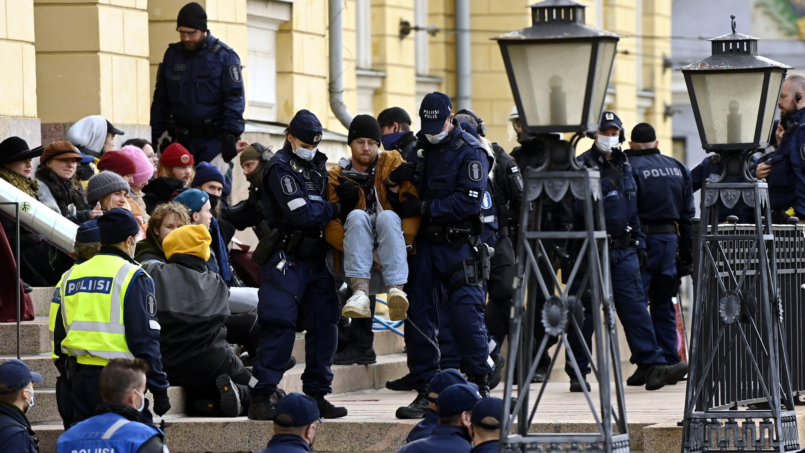 Poliisi siirtää mielenosoittajia pois paikalta - Ympäristöliike Elokapina lukittautui Valtioneuvoston linnan edustalle Helsingissä 8. lokakuuta 2021.
